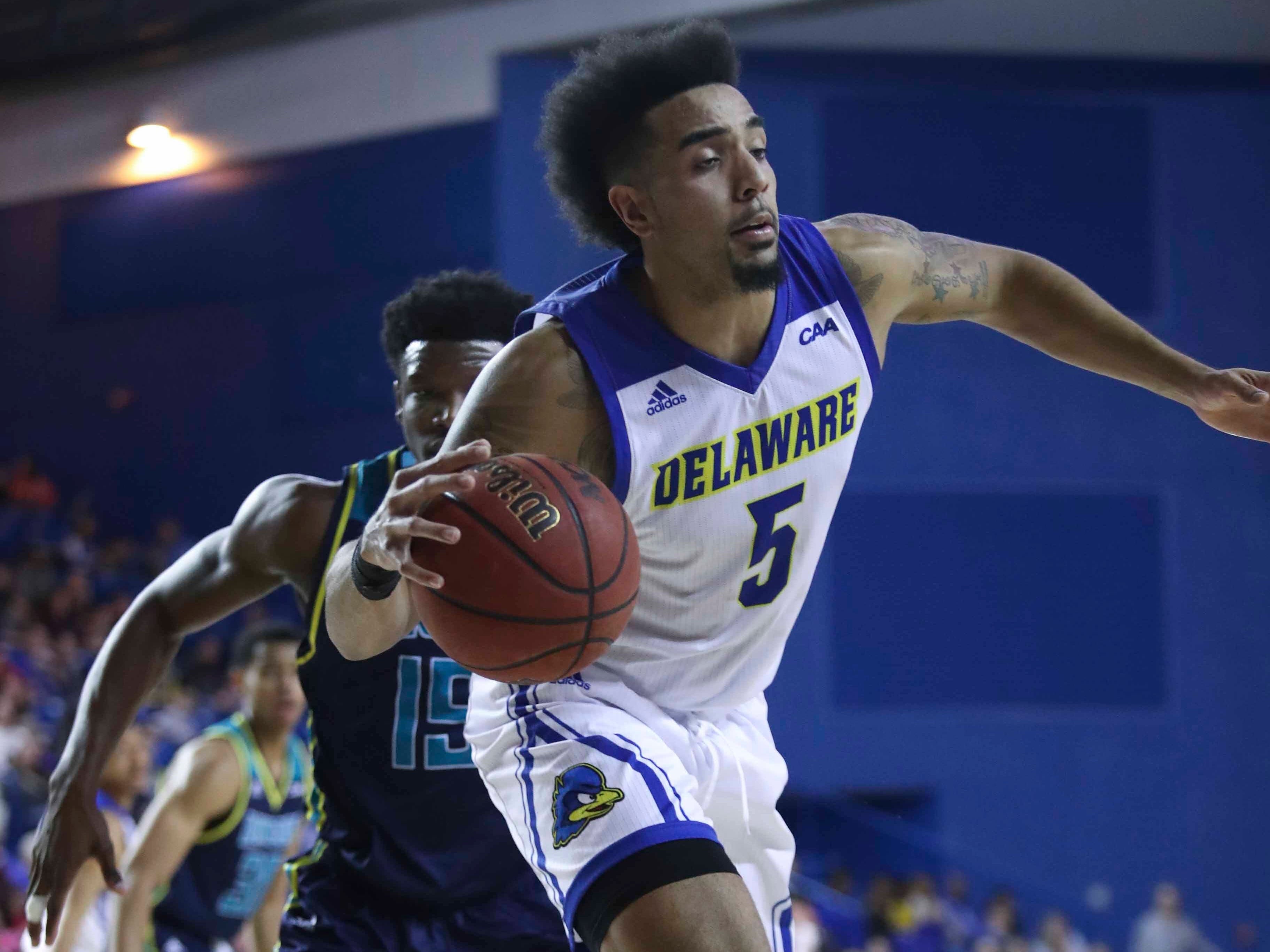 Delaware's Eric Carter is knocked off balance by UNC-Wilmington's Devontae Cacok in the second half of Delaware's 70-66 win at the Bob Carpenter Center Saturday.