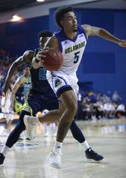 Delaware's Eric Carter is knocked off balance by UNC-Wilmington's Devontae Cacok in the second half of Delaware's 70-66 win at the Bob Carpenter Center.