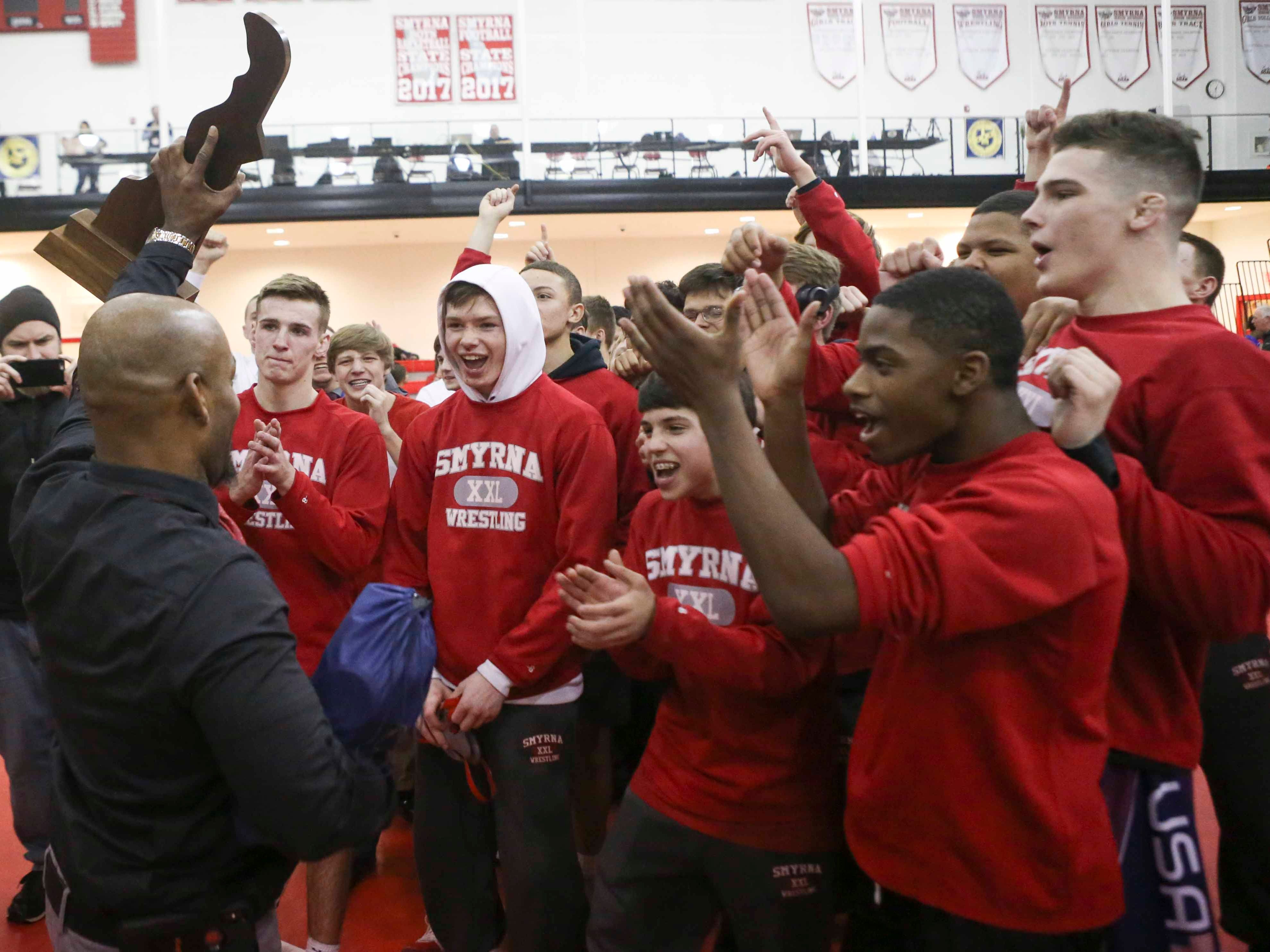 Smyrna head coach Aaron Harris (left) delivers the title trophy to his DIAA state high school Division I dual meet champions Saturday at Smyrna High School.