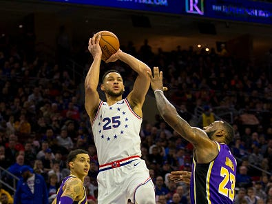 Ben Simmons #25 of the Philadelphia 76ers shoots the ball against LeBron James #23 of the Los Angeles Lakers in the second quarter at the Wells Fargo Center on February 10, 2019 in Philadelphia.