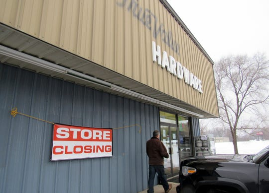 In this Jan. 22, 2019, photo a person walks by the Poynette True Value Hardware in Poynette, Wis.