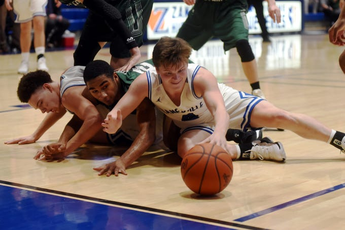 Zanesville's Clayton Foreman reaches for a loose ball along the baseline durign the fourth quarter of the Blue Devils' 52-42 loss to Canton Central Catholic on Saturday night at Winland Memorial Gymnasium.
