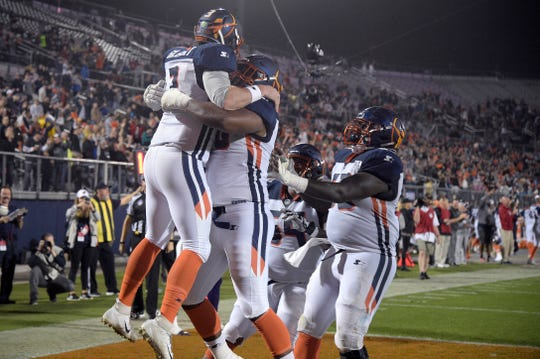 Orlando Apollos quarterback Garrett Gilbert, left, is congratulated by teammates after catching a pass from receiver Jalin Marshall for a 5-yard touchdown during the first half of an Alliance of American Ffootball game against the Atlanta Legends on Feb. 9, 2019.