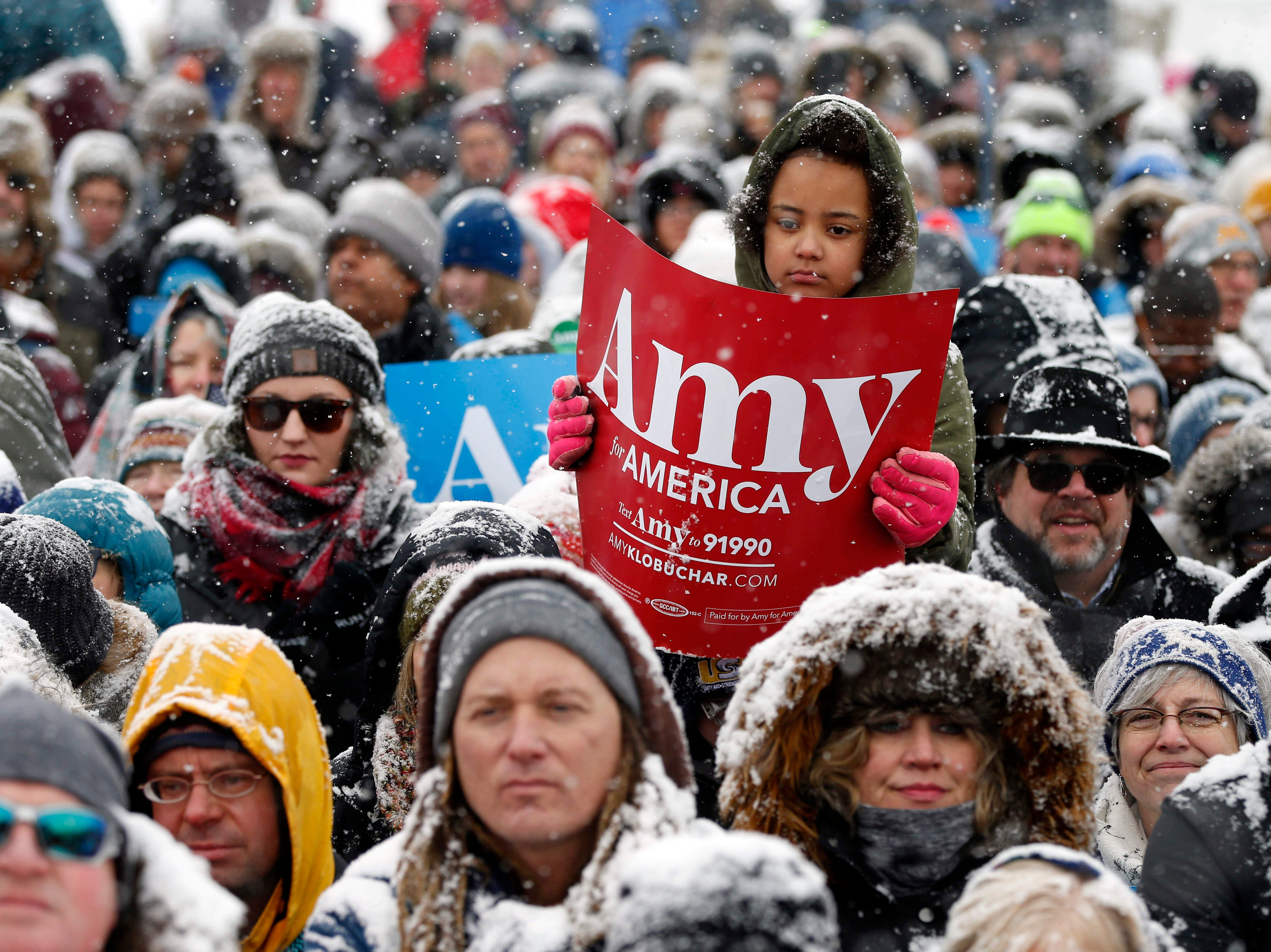 A young person holds a sign as Democratic Sen. Amy Klobuchar of Minnesota announces she is entering the race for president during a rally Sunday, Feb. 10, 2019, at Boom Island Park in Minneapolis.