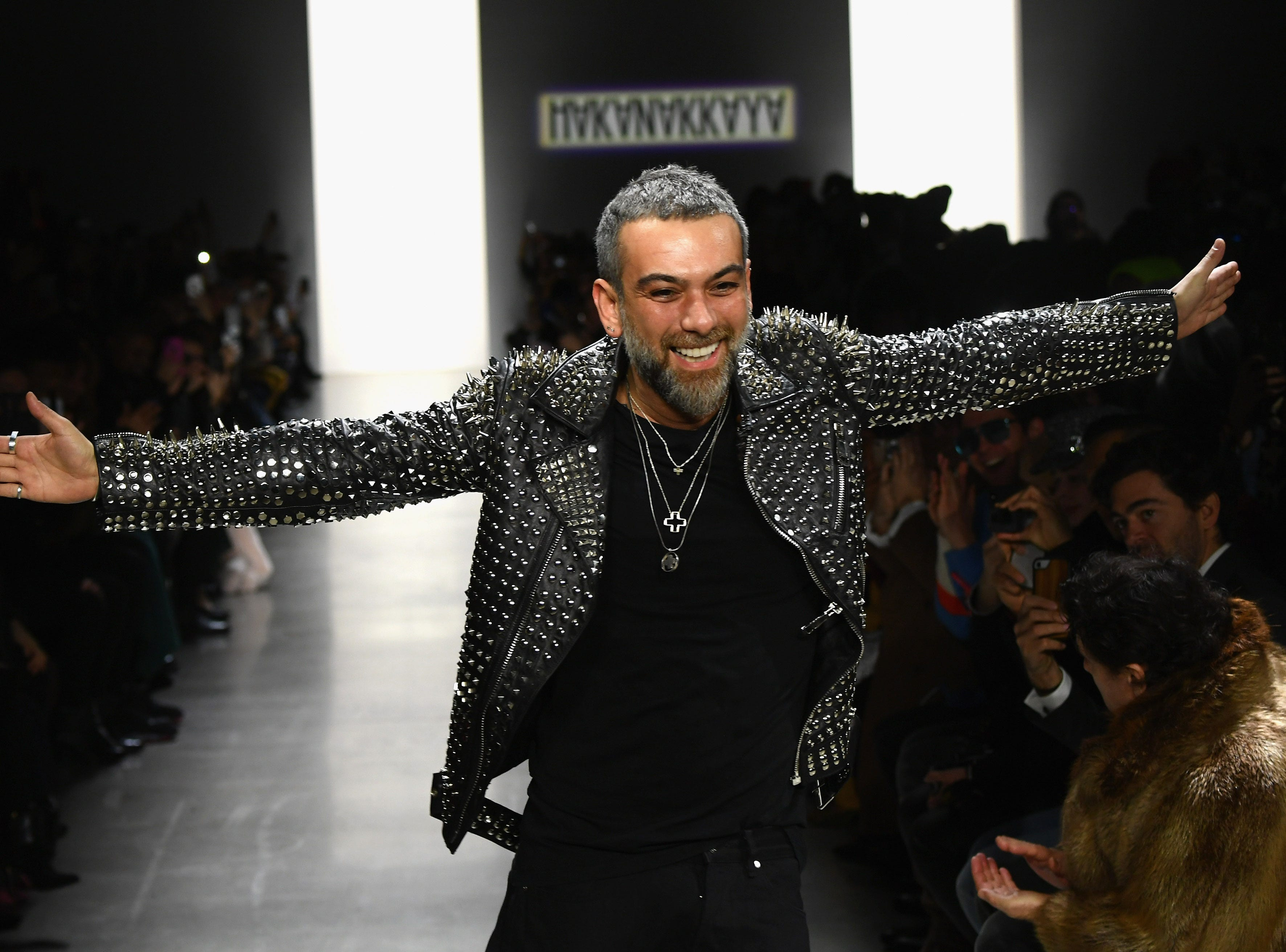 Designer Hakan Akkaya excitedly walks down the runway at his own show.