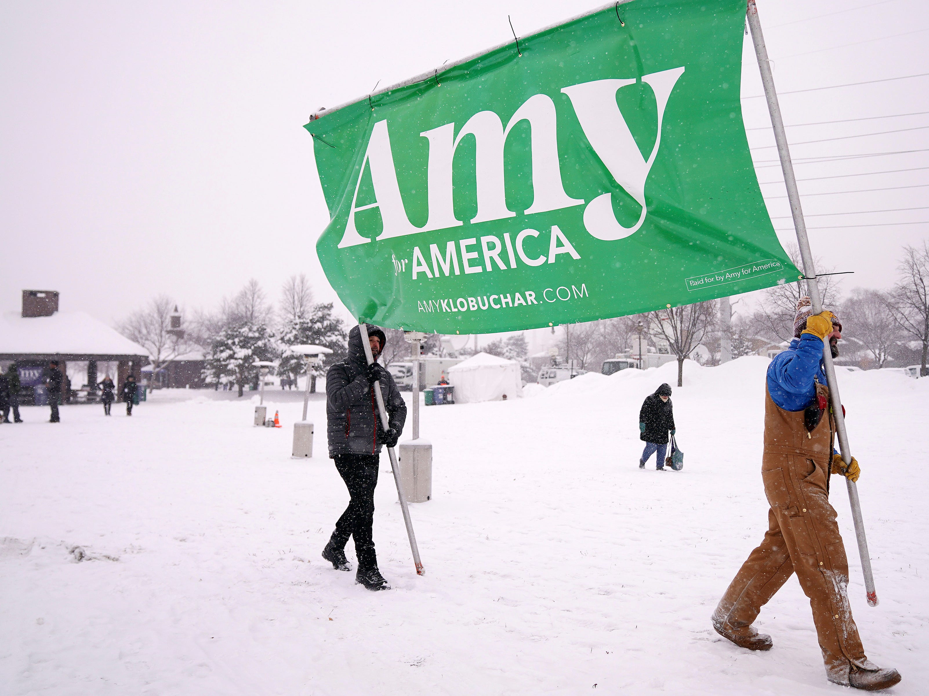 """Volunteers Tim Schumann, left, and Chase Cushman move an """"Amy for America"""" sign into place Sunday, Feb. 10, 2019, prior to Democratic Sen. Amy Klobuchar's announcement of her decision in the race for president at a rally in Minneapolis."""