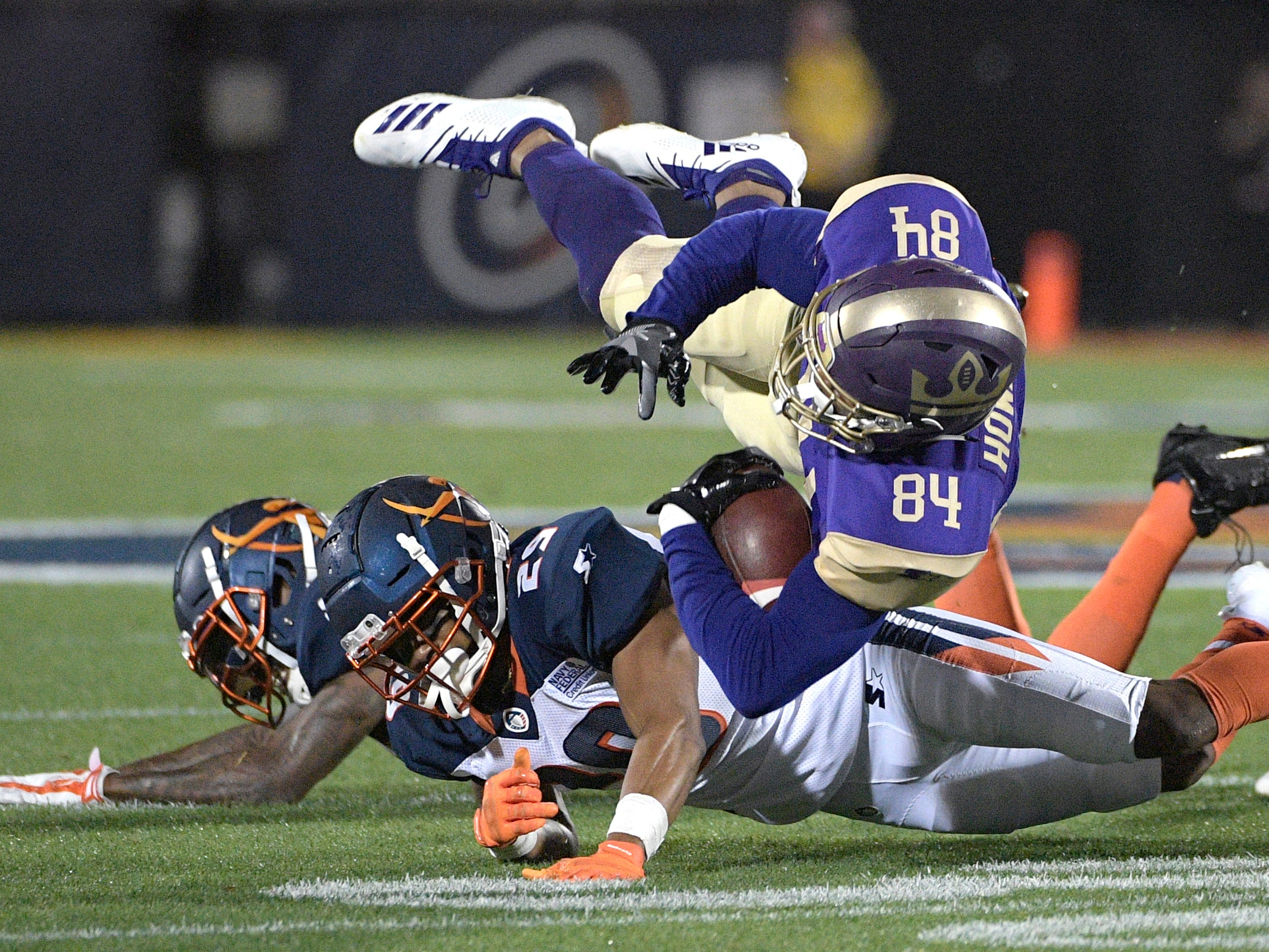 Atlanta Legends receiver Bug Howard (84) is tackled by Orlando Apollos safety Will Hill and defensive back Keith Reaser (29) after catching a pass during the first half of an Alliance of American Football game.