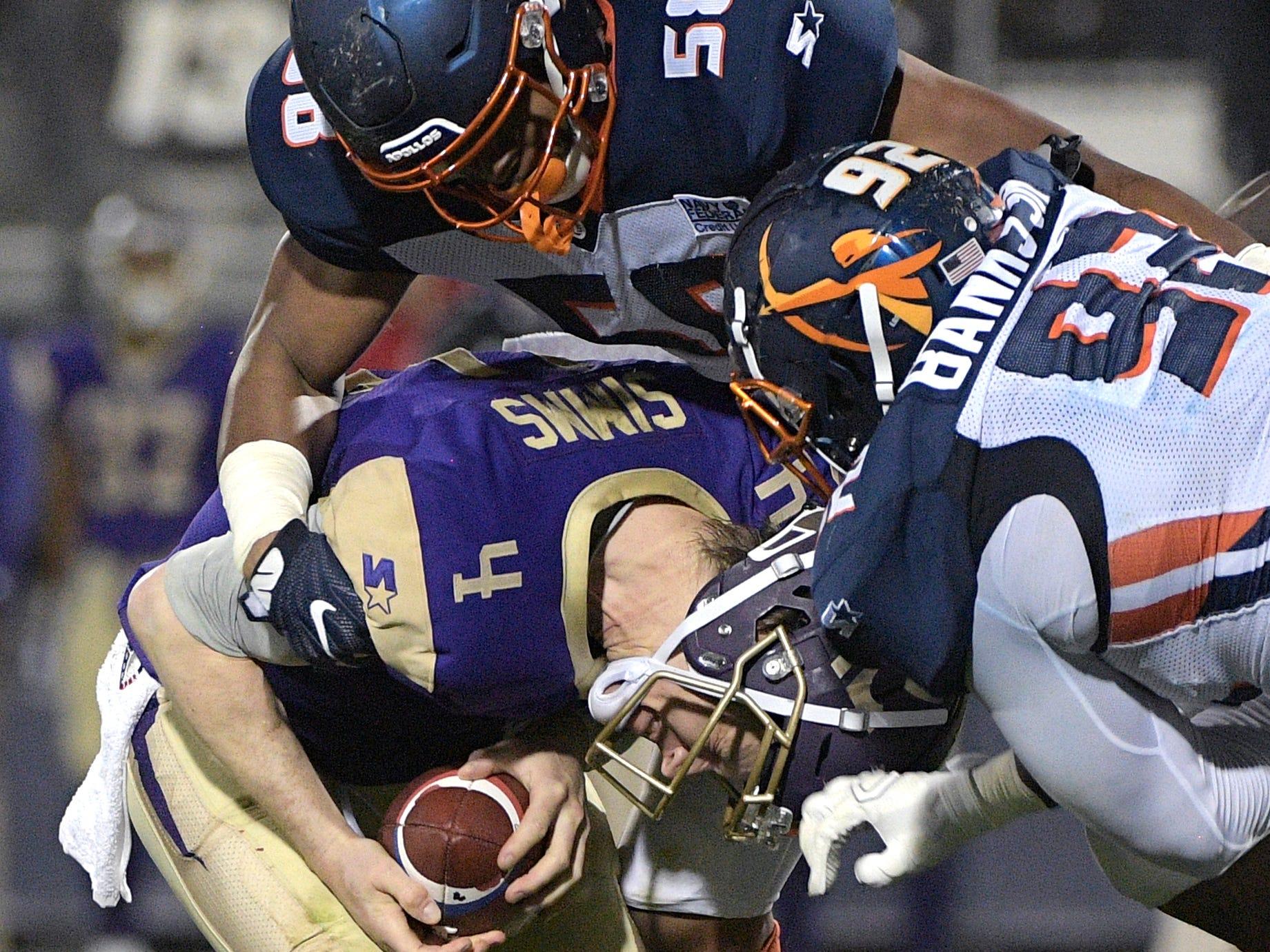 Atlanta Legends quarterback Matt Simms (4) is sacked by Orlando Apollos linebacker Christian French (58) and Josh Banks Sr. (92).