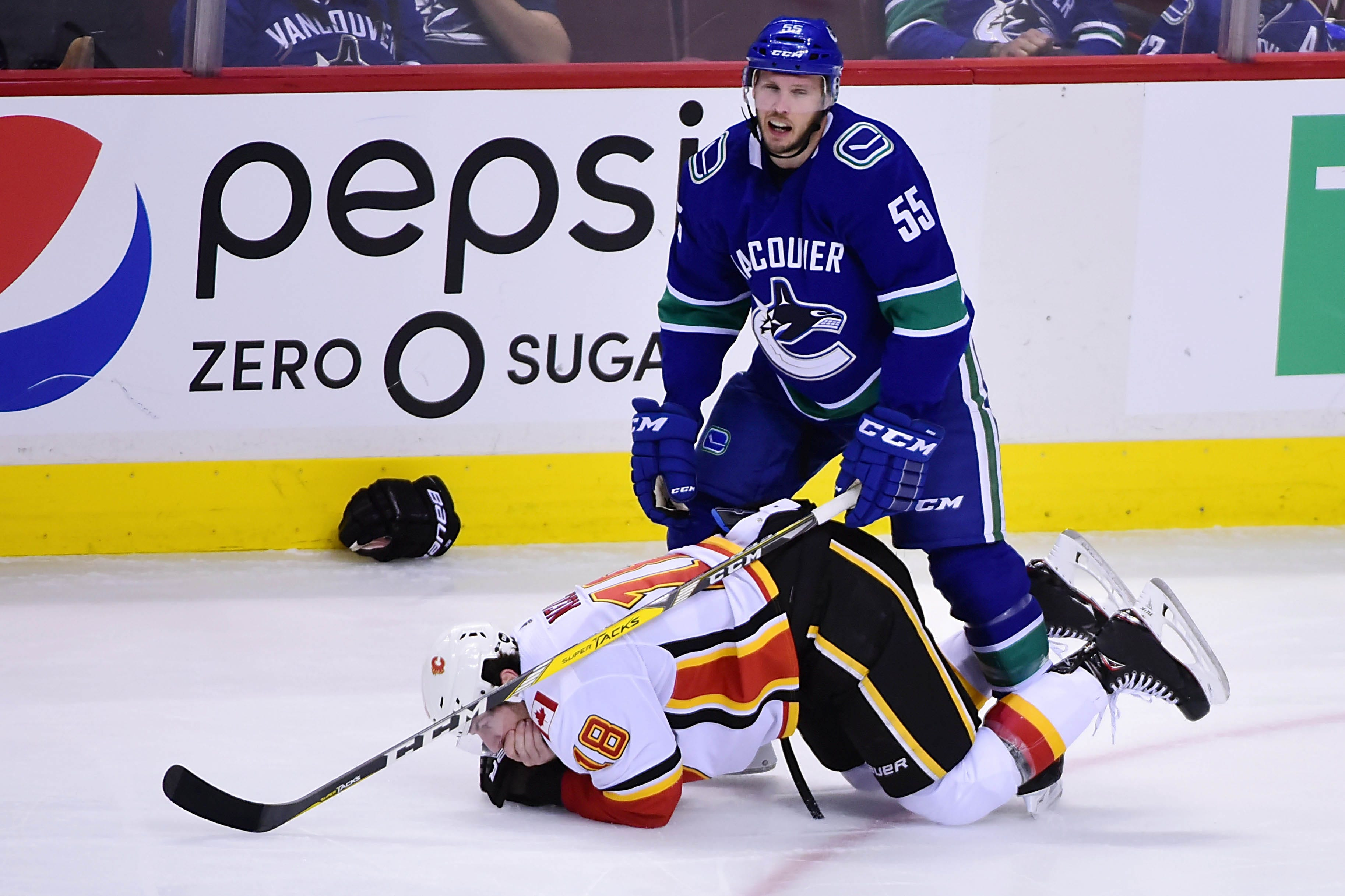 Calgary Flames forward James Neal grabs his mouth after he is high-sticked by Vancouver Canucks defenseman Alex Biega.