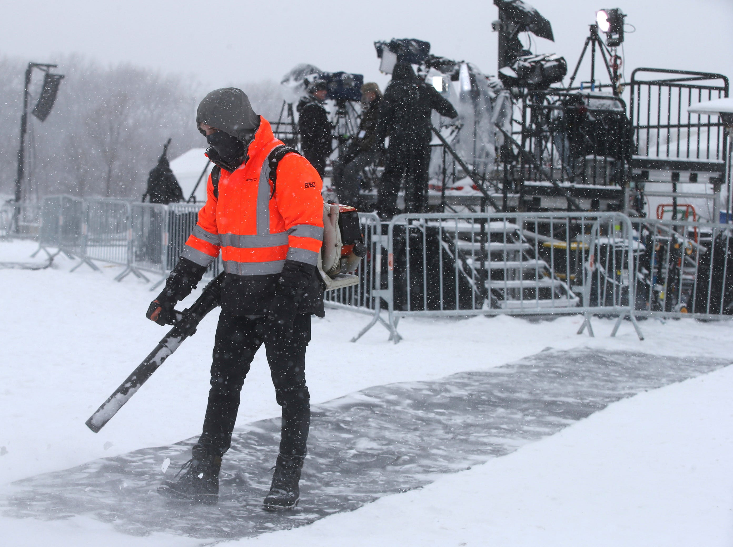 Snow continues to fall as a worker clears snow off a runner and media members arrange equipment on a riser prior to Democratic Sen. Amy Klobuchar's announcement of her decision in the race for president at a rally Sunday, Feb. 10, 2019, at Boom Island Park in Minneapolis.