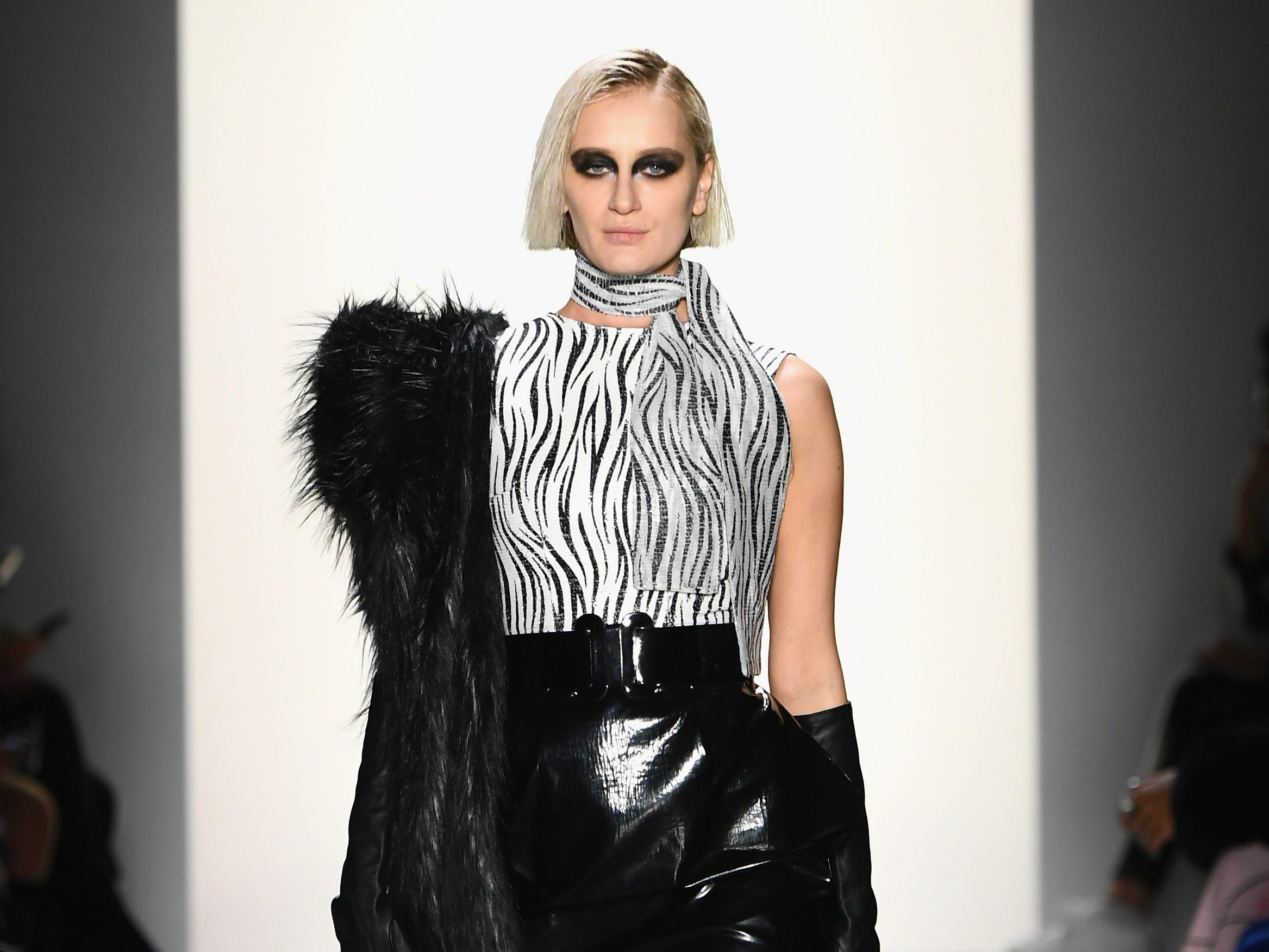 A model wears Hakan Akkaya's 2019 Fall designs as she makes her way down the runway.