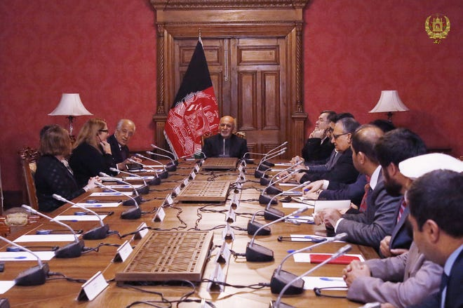 U.S. envoy Zalmay Khalilzad, left, briefs  Afghan President Ashraf Ghani, center, in Kabul on Jan. 27, 2019.