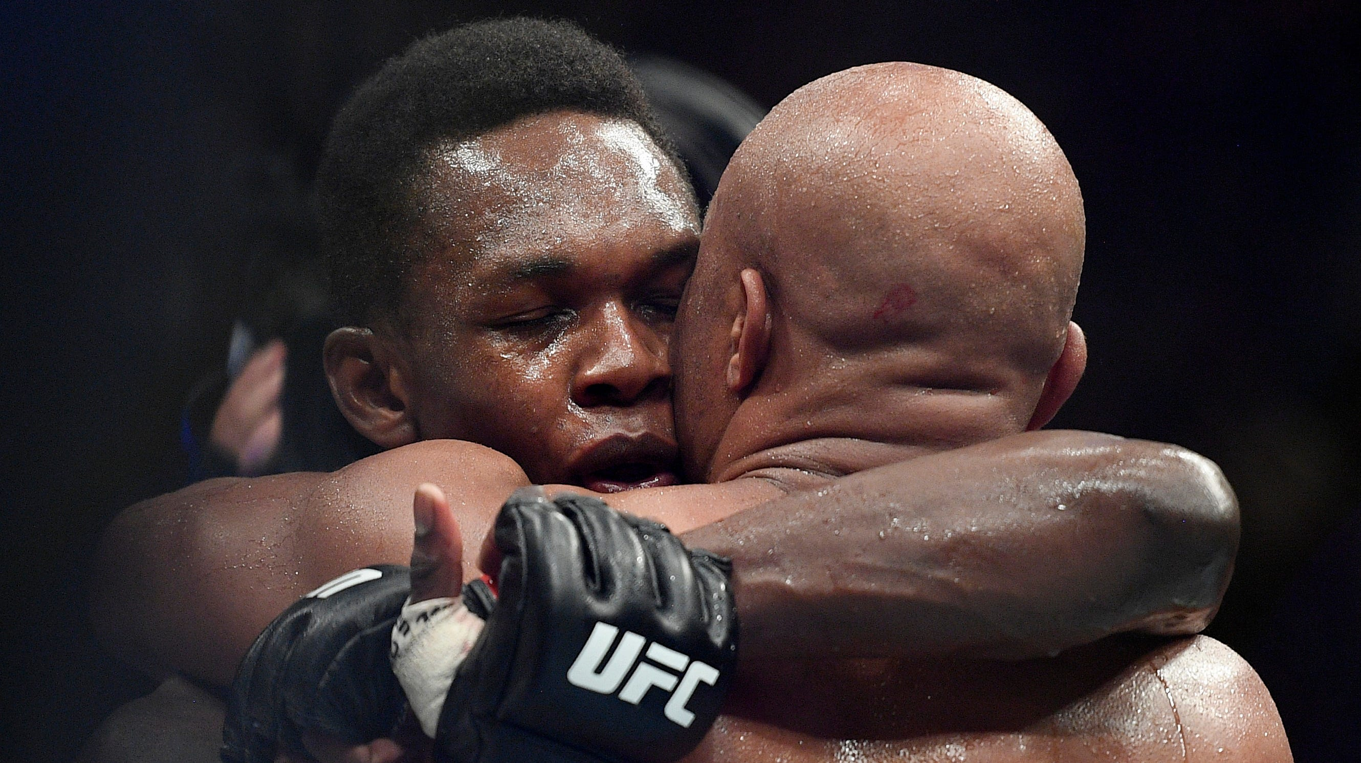 Israel Adesanya, left, hugs Anderson Silva after winning their middleweight bout at the UFC 234.