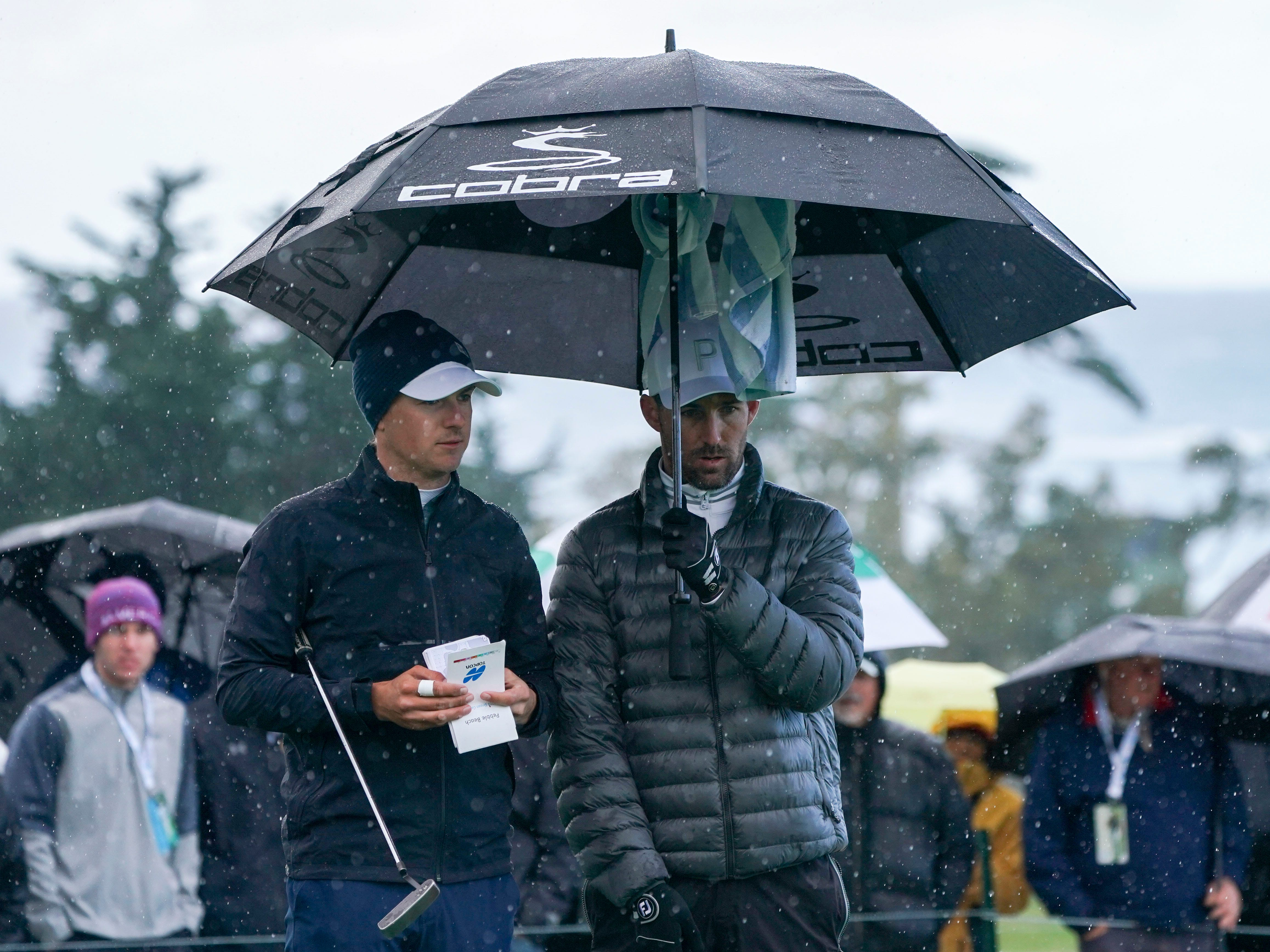 Jordan Spieth (left) and Jake Owen (right) stand under an umbrella on the second hole during the final round of the AT&T Pebble Beach Pro-Am.