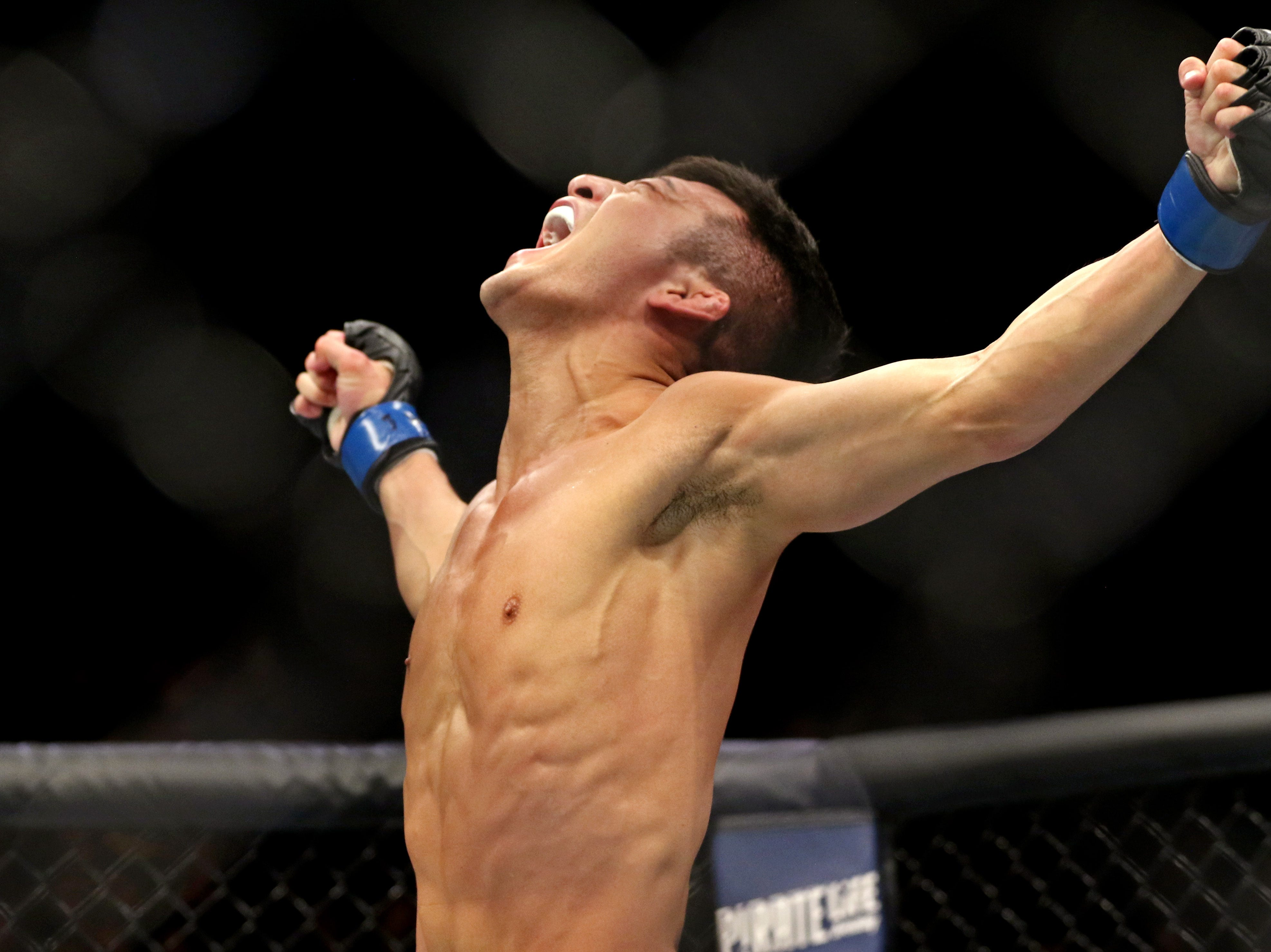 Kyung Ho Kang (blue gloves) celebrates beating Teruto Ishihara (red gloves) during UFC 234 at Rod Laver Arena.