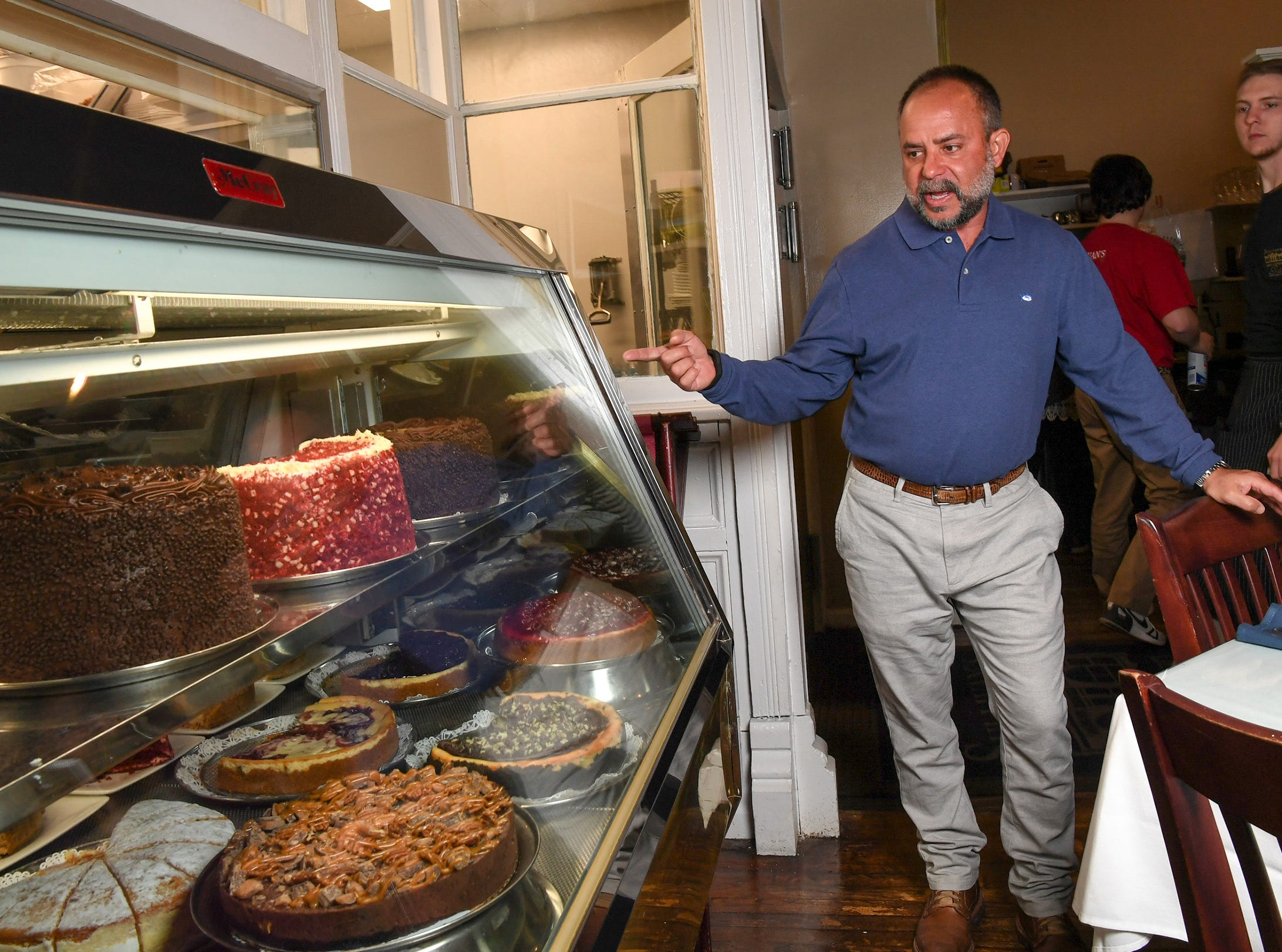 Bill Nickas, co-owner of Sullivan's Metropolitan Grill in Anderson, looks at cheesecakes and cakes his wife Sabra Nickas makes and many love at the downtown Anderson restaurant.