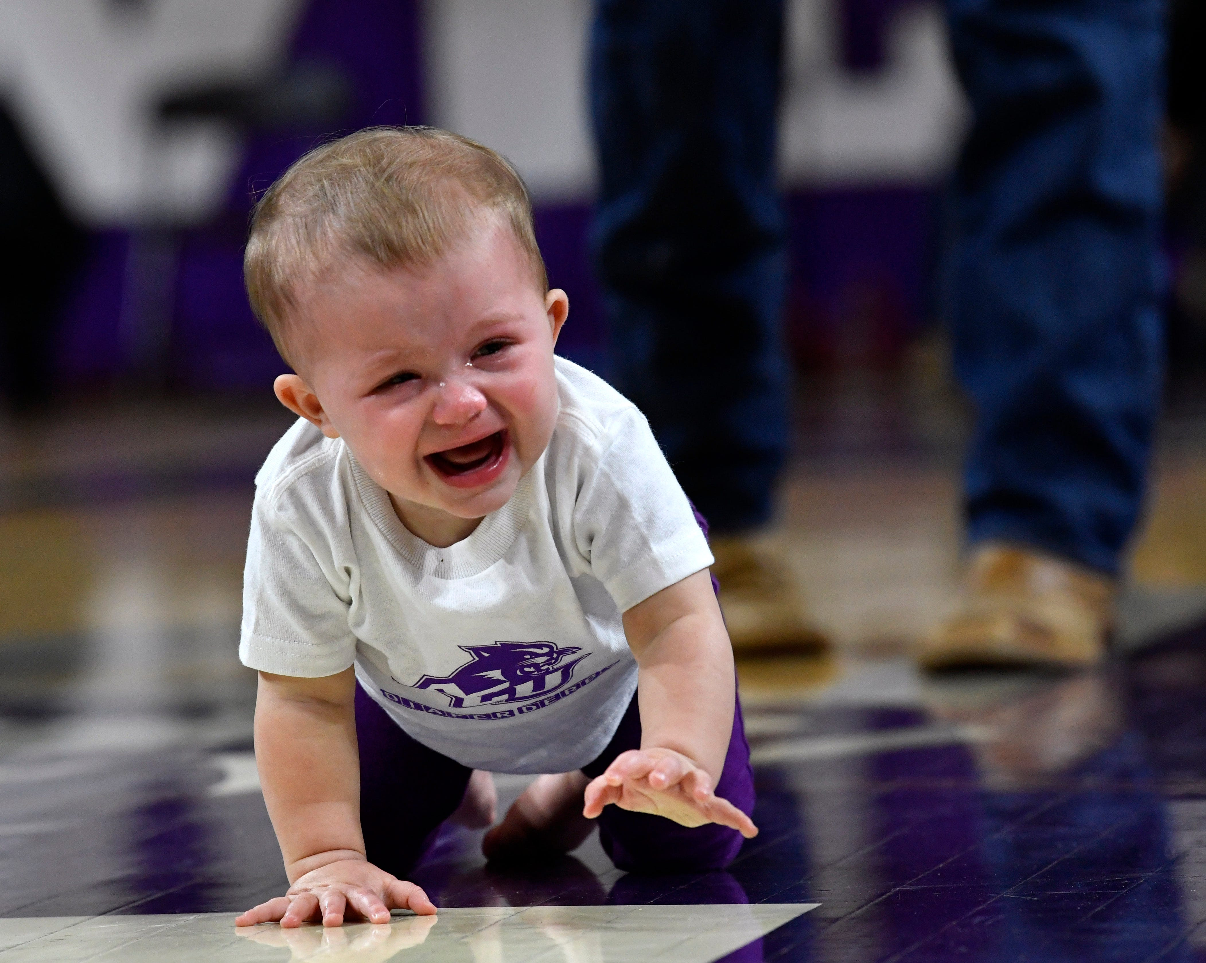 Trinity Brady cries while crawling toward her mother Jamie before stopping in the middle of the court at Moody Coliseum and plopping down.