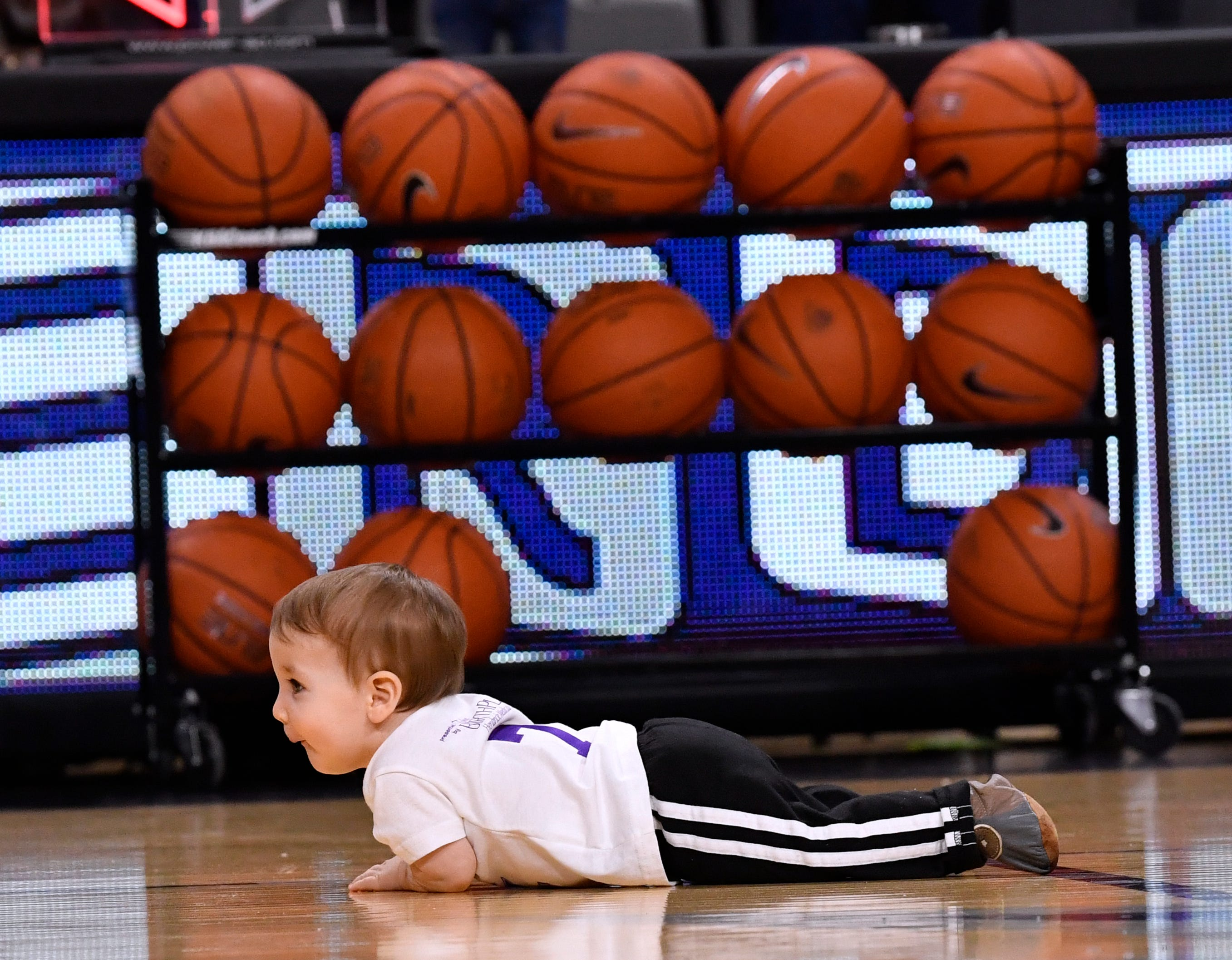 """Logan Macaluso paused to """"plank"""" in the middle of the court at Moody Coliseum before continuing on to his mother Suzie."""