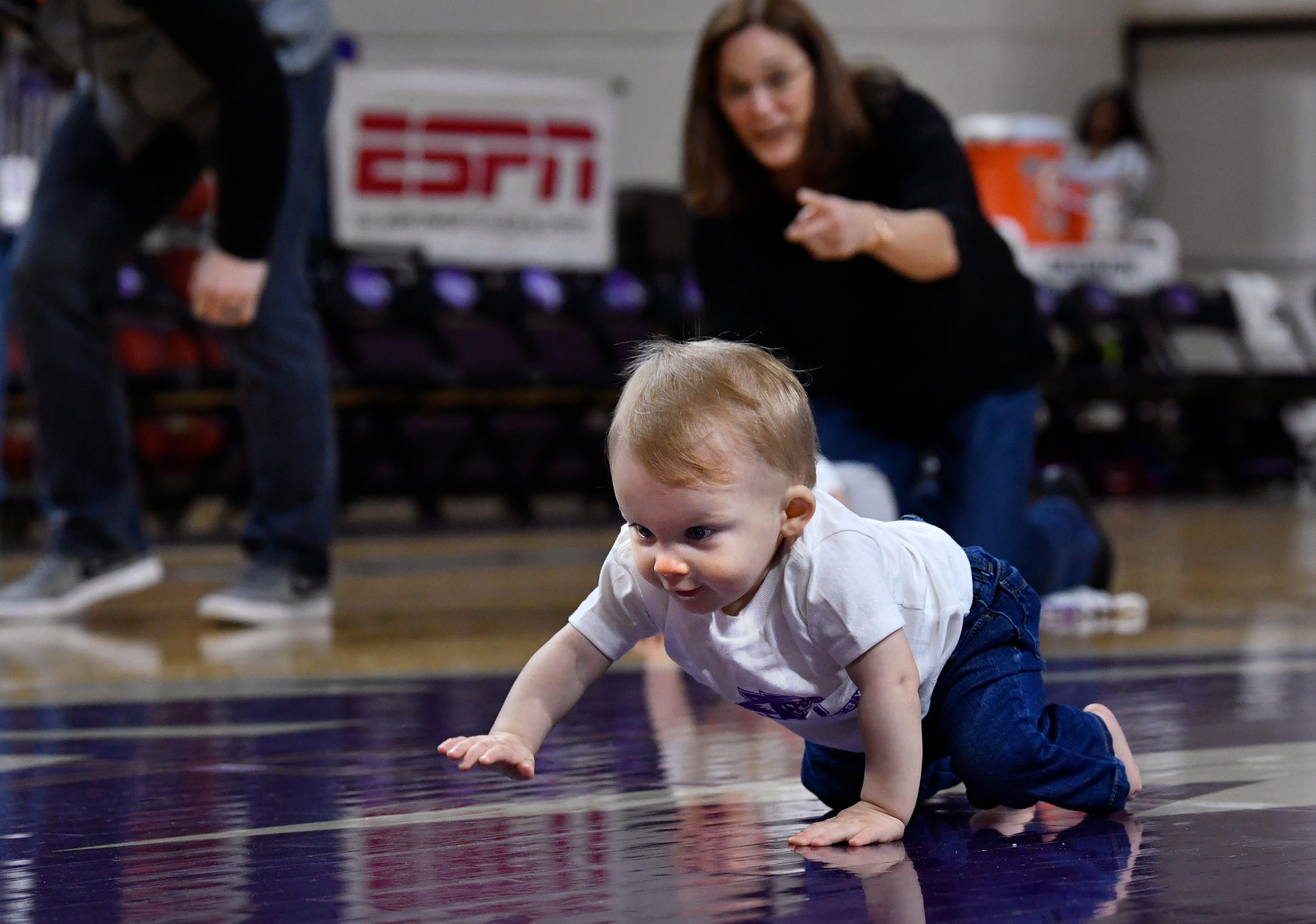 Oliver Glover crawls across the court at Moody Coliseum toward his mother Kaytlin on Jan. 26. Abilene Christian University held a Diaper Derby during halftime at both men's and women's basketball games.