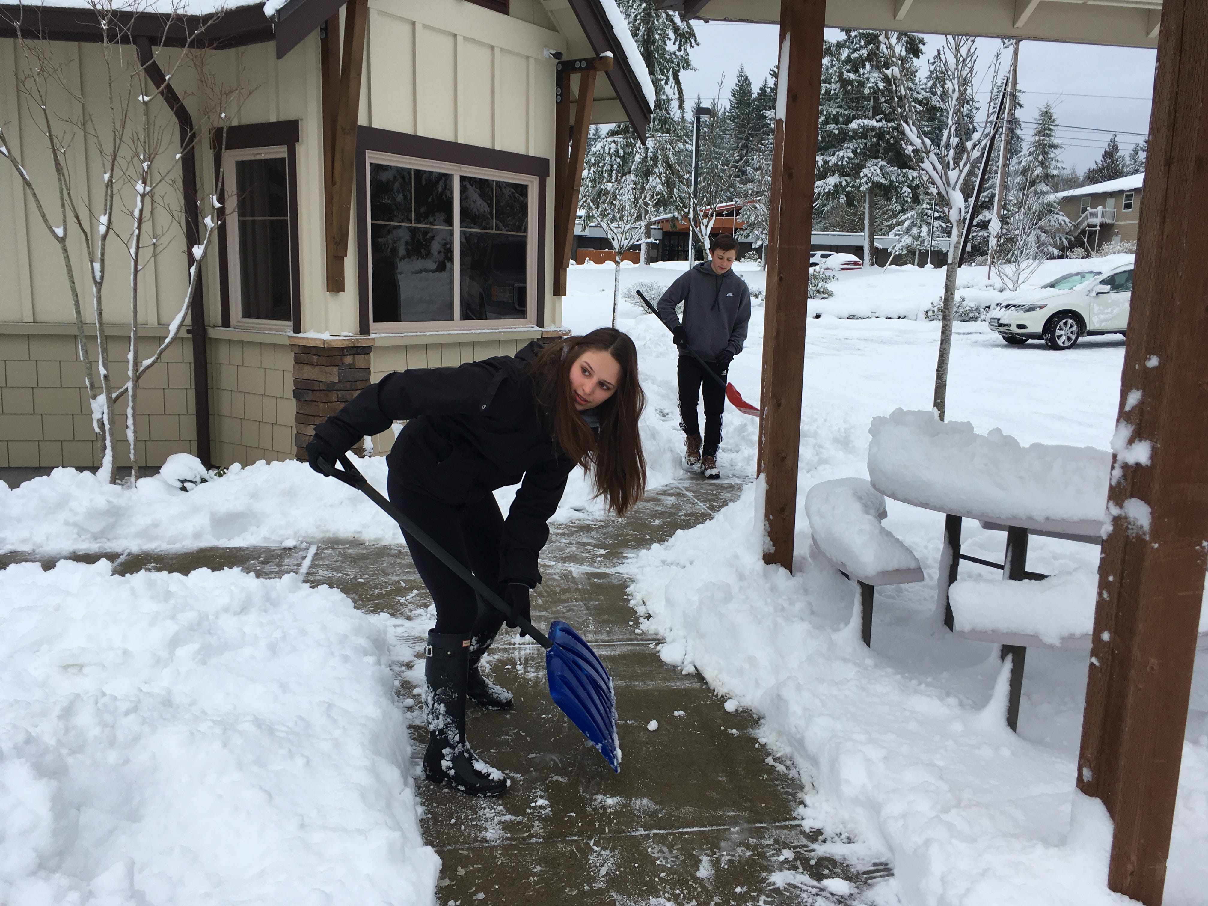 Clara Bock, 16, and Lukas Bock, 14, shovel snow on the sidewalk of South Kitsap Family Dentistry in Port Orchard on Feb. 11, 2019. Their father Dr. Chris Bock was at the office for emergency cases only given the snow that closed schools and many businesses around Kitsap County.