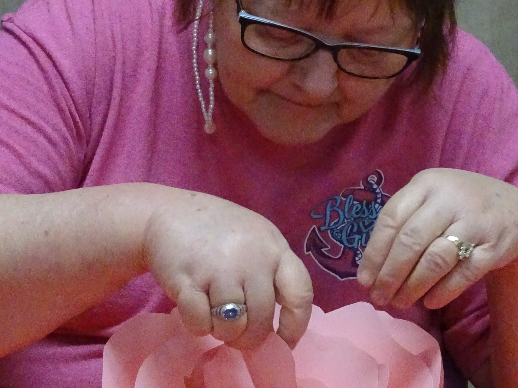 Gloria Pelfrey, 63, Bucyrus, adds petals to the center of her paper rose during a program at the Crawford County Council on Aging office on Monday afternoon.