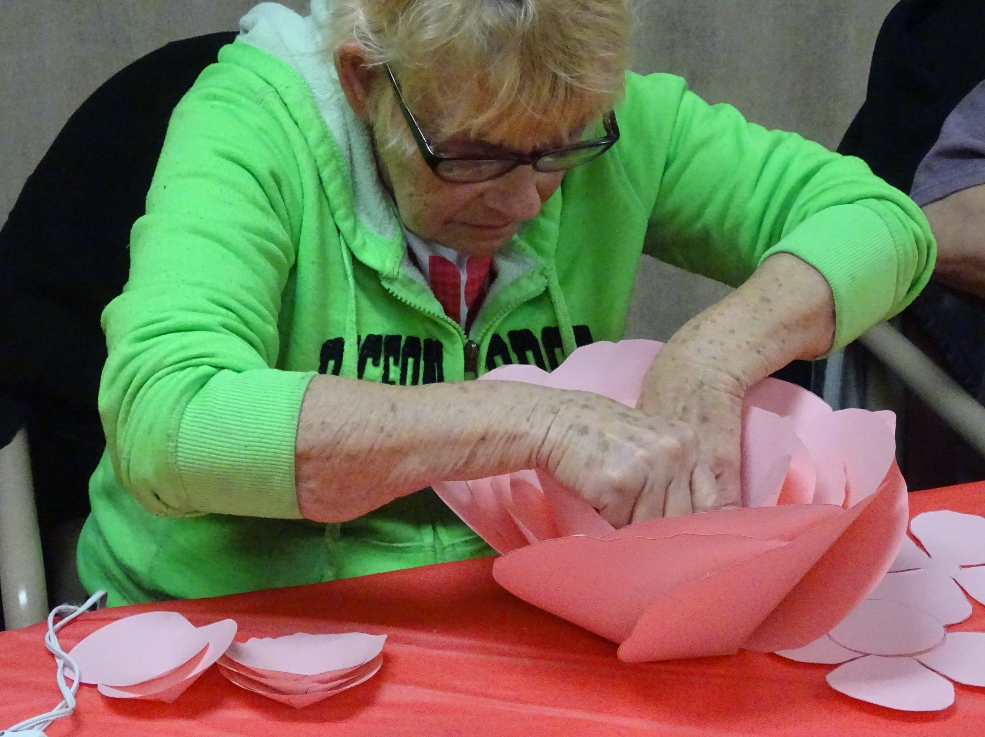 Participants in a craft program at the Crawford County Council on Aging make big, pink paper roses on Monday.