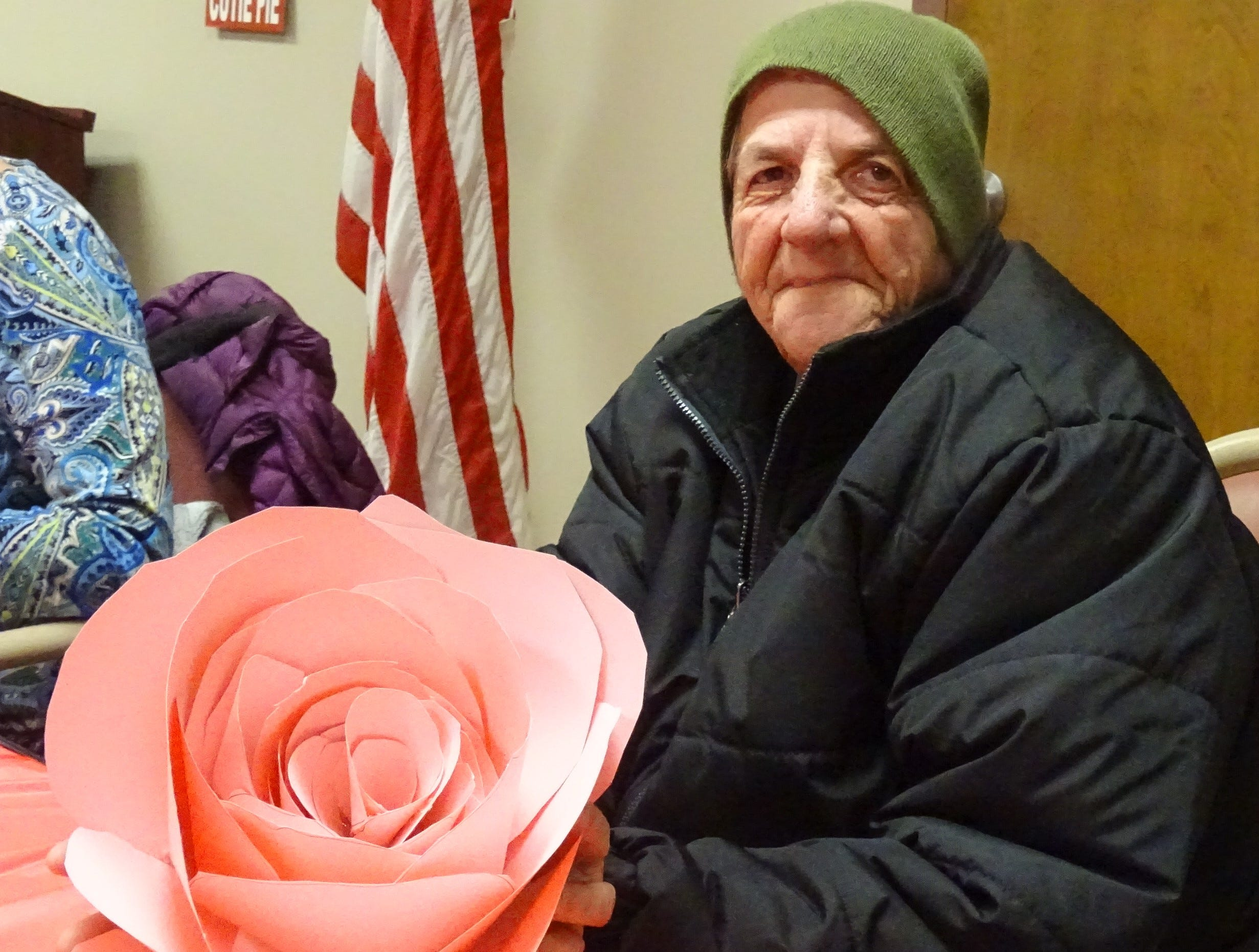 Dorothy Paloman, 74, Bucyrus, shows off her completed paper rose during a program at the Crawford County Council on Aging office on Monday afternoon.