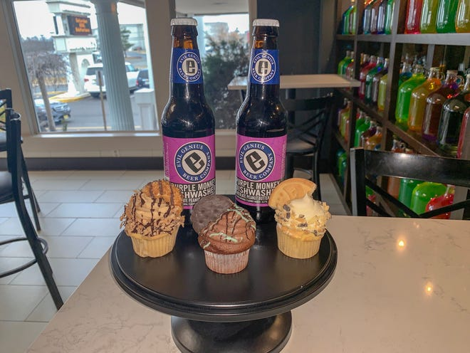 """Adelphia's """"Milk and Cookies"""" offering for grown-ups features three mini cupcakes topped with Samoas, Caramel Delites, Tagalongs and Thin Mints. The dessert flight is paired with a pint of Evil Genius Purple Monkey Dishwasher (6.7% ABV)."""