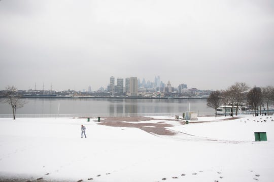 A man exercises along the Camden Waterfront following snowfall in the region Monday, Feb. 11, 2019 in Camden, N.J.