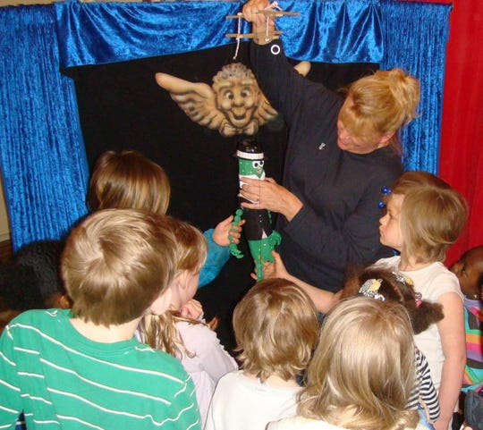 Puppeteer Linda Mason demonstrating a puppet for children.