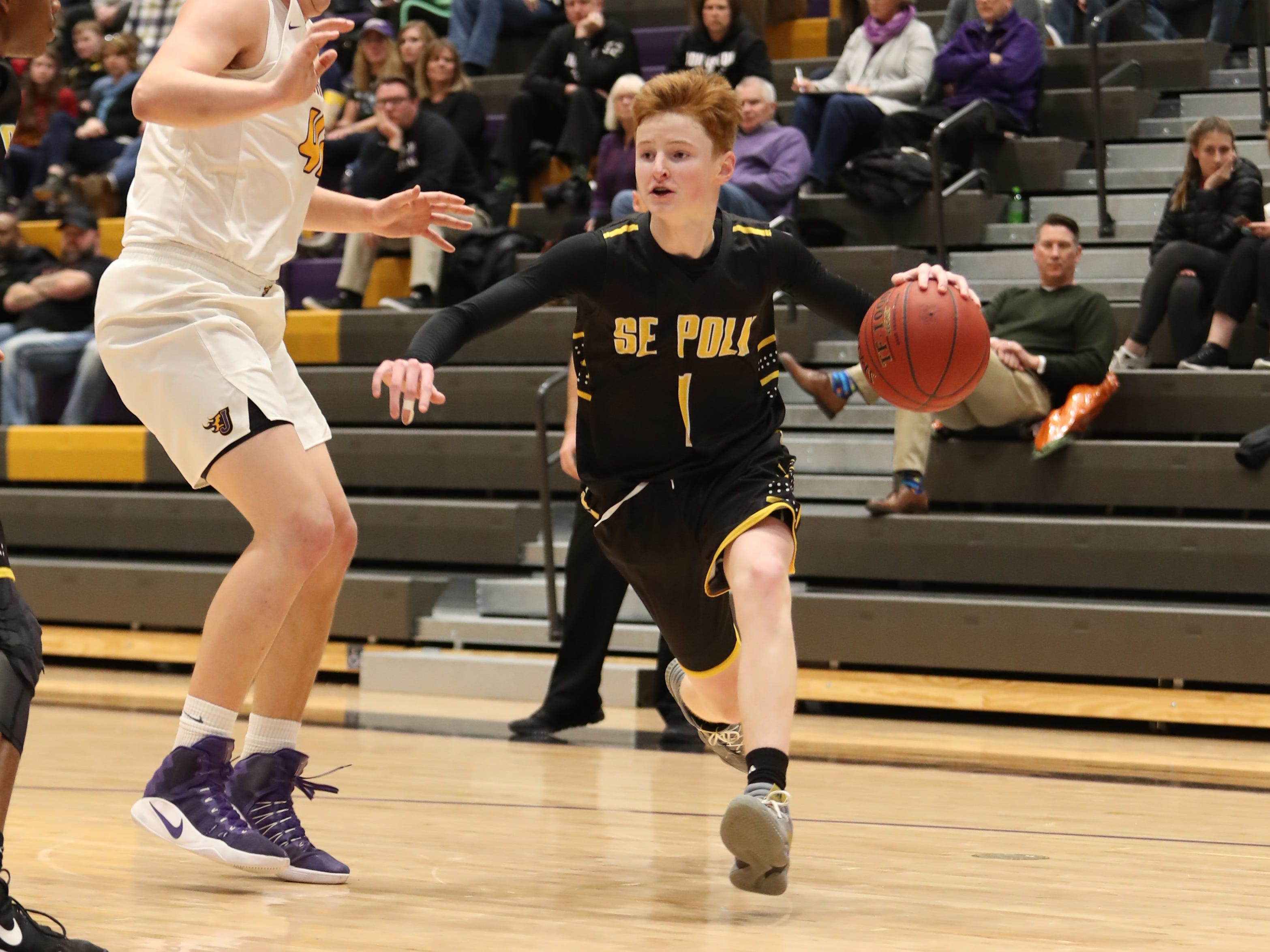 Southeast Polk's James Glenn (1) drives to the basket against the Dragons' defense Feb. 5 at Johnston High School. Glenn hit four 3-pointers for 16 points.