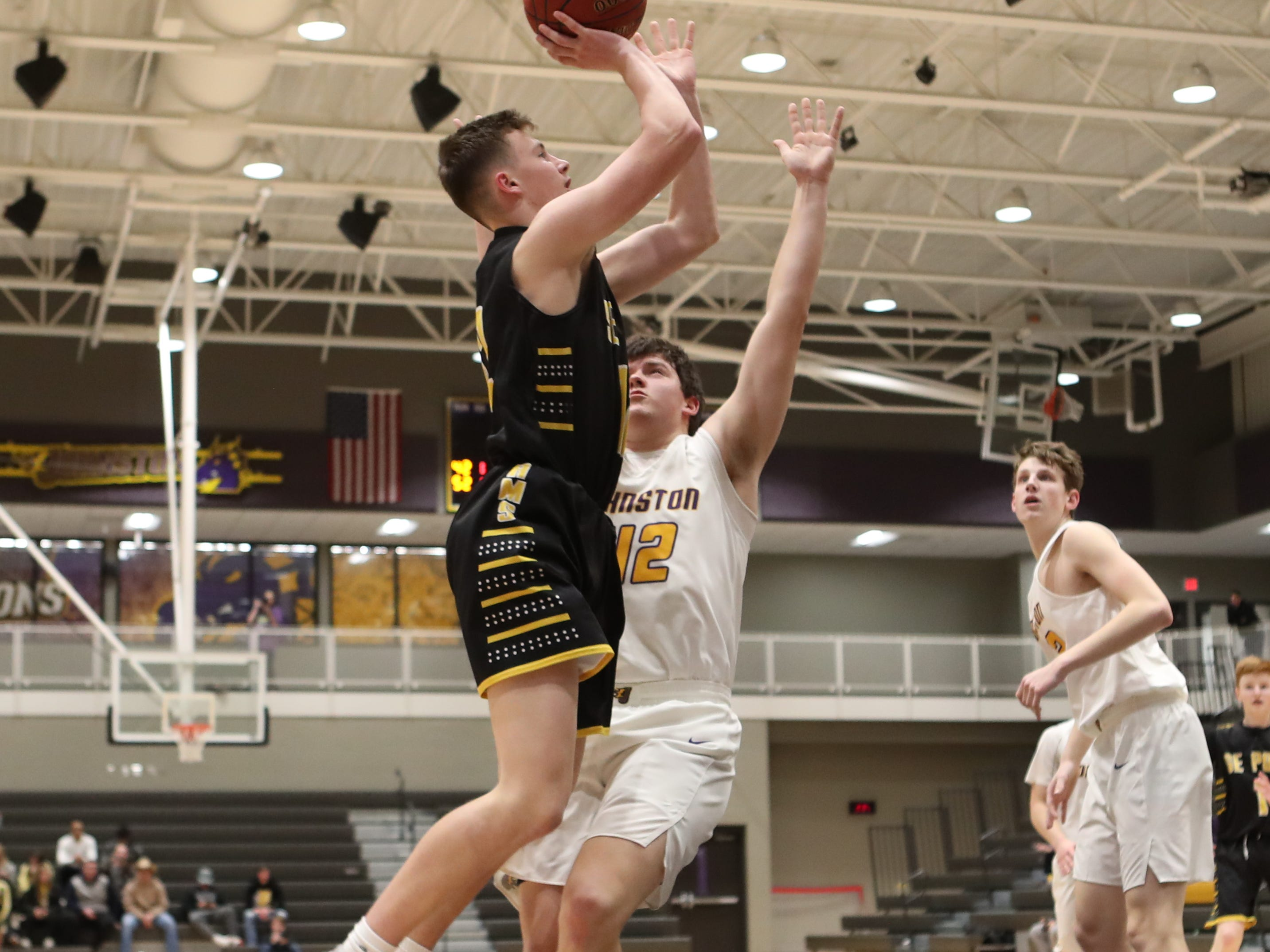 Southeast Polk's Fred Johnson (12) shoots over the top of the Johnston defense in a Feb. 5 game at Johnston High School. Johnston won the game 51-44.