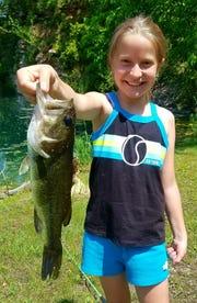 Ella Kisner of Oelwein, Iowa, with a bass caught in a rural Buchanan County pond.