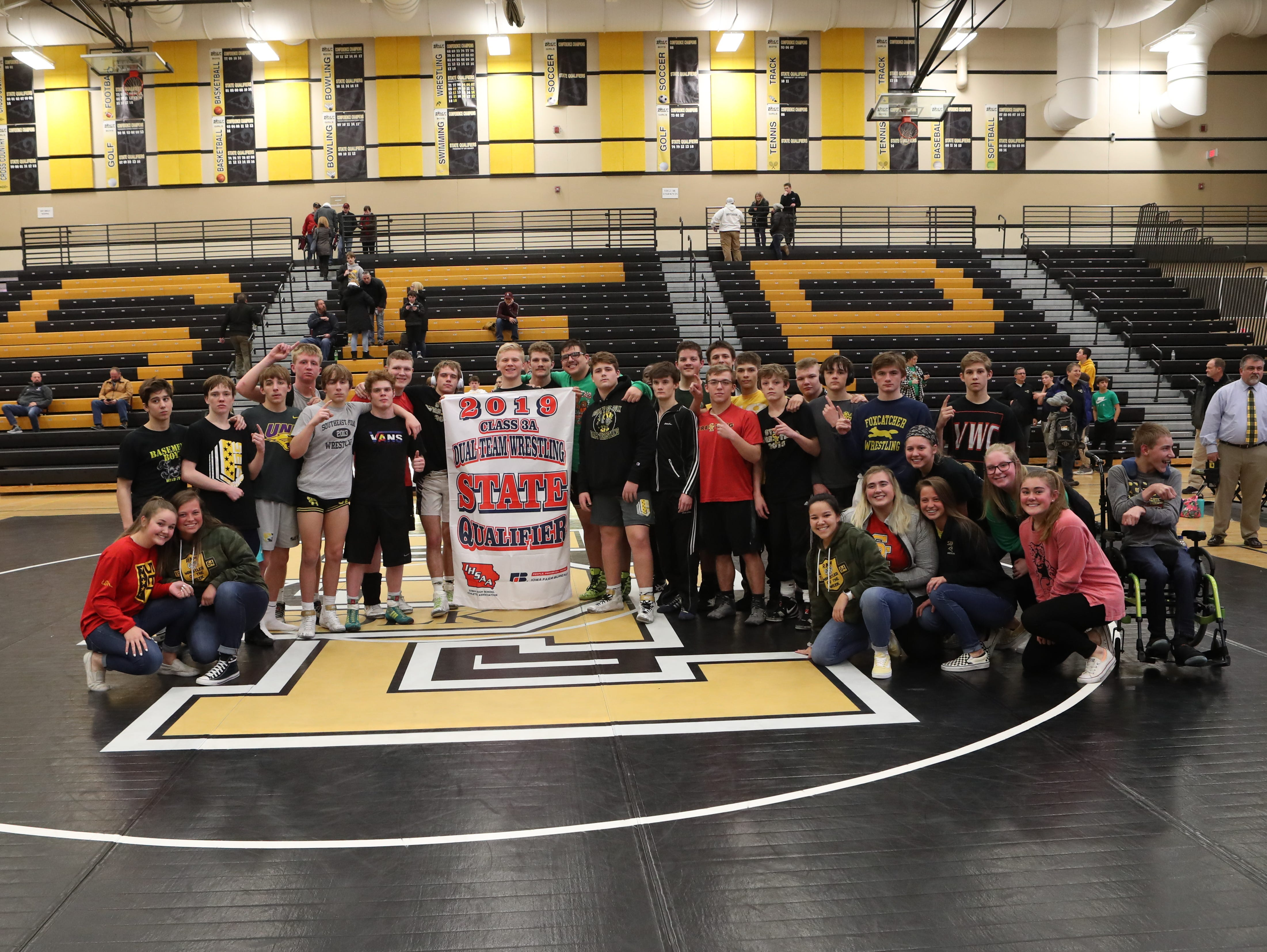 Southeast Polk wrestlers hold their state qualifier banner after beating Ankeny   57-17 in a Class 3A regional dual Feb. 6 at Southeast Polk.