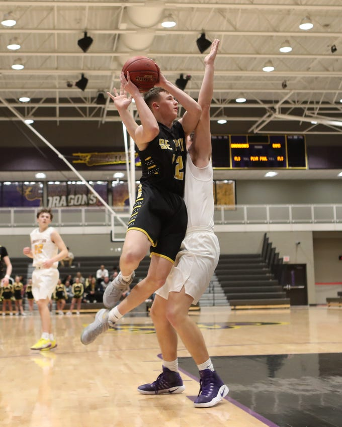 Southeast Polk's Fred Johnson (12) shoots over the top of a Johnston defender Feb. 5 at Johnston High School. Johnston won the game 51-44.