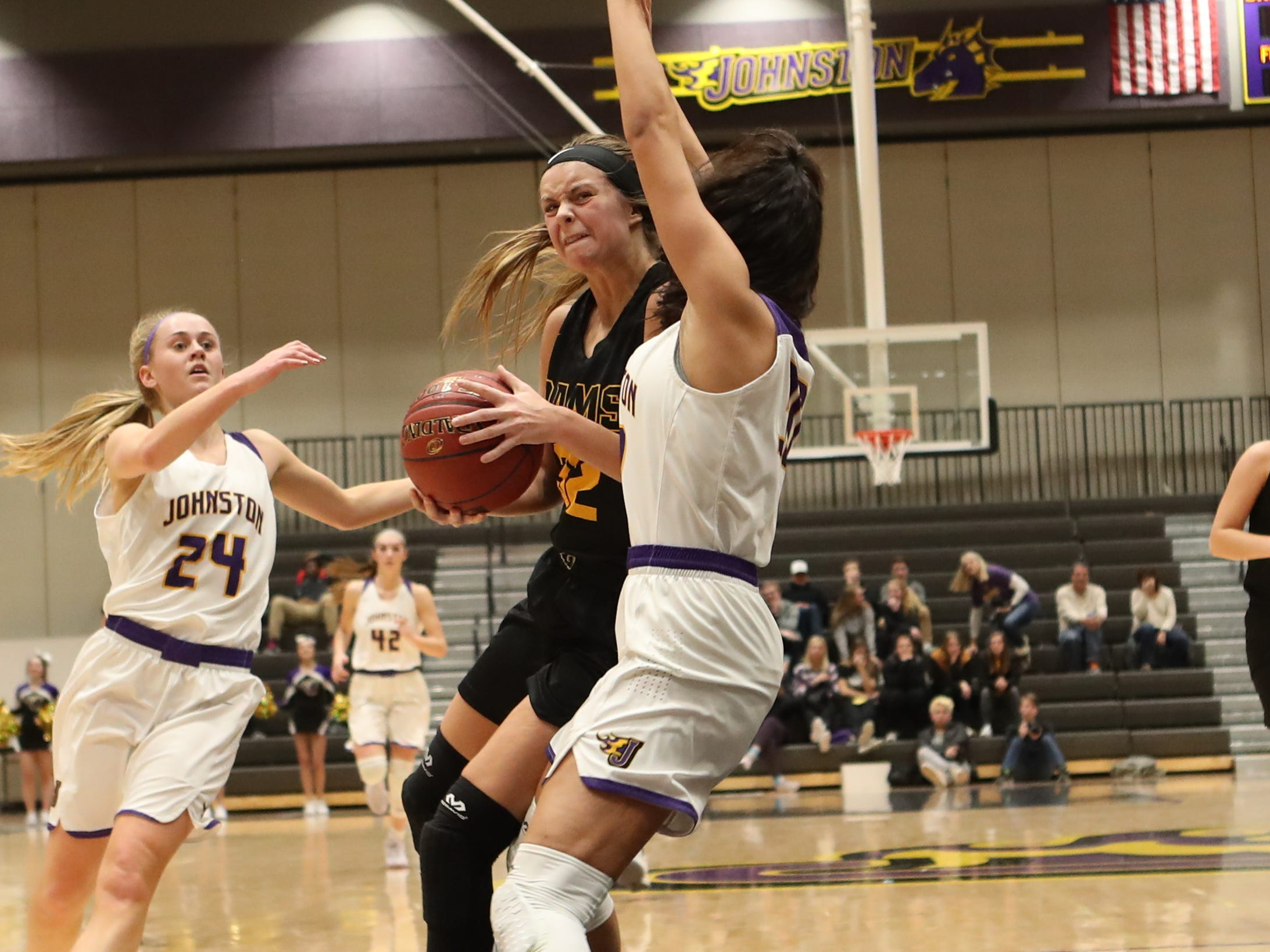 Southeast Polk's Maggie McGraw (32) runs into a defender Feb. 5 in a game against No. 1 Johnston at Johnston High School. The Dragons won the game 89-67. McGraw had 23 points.