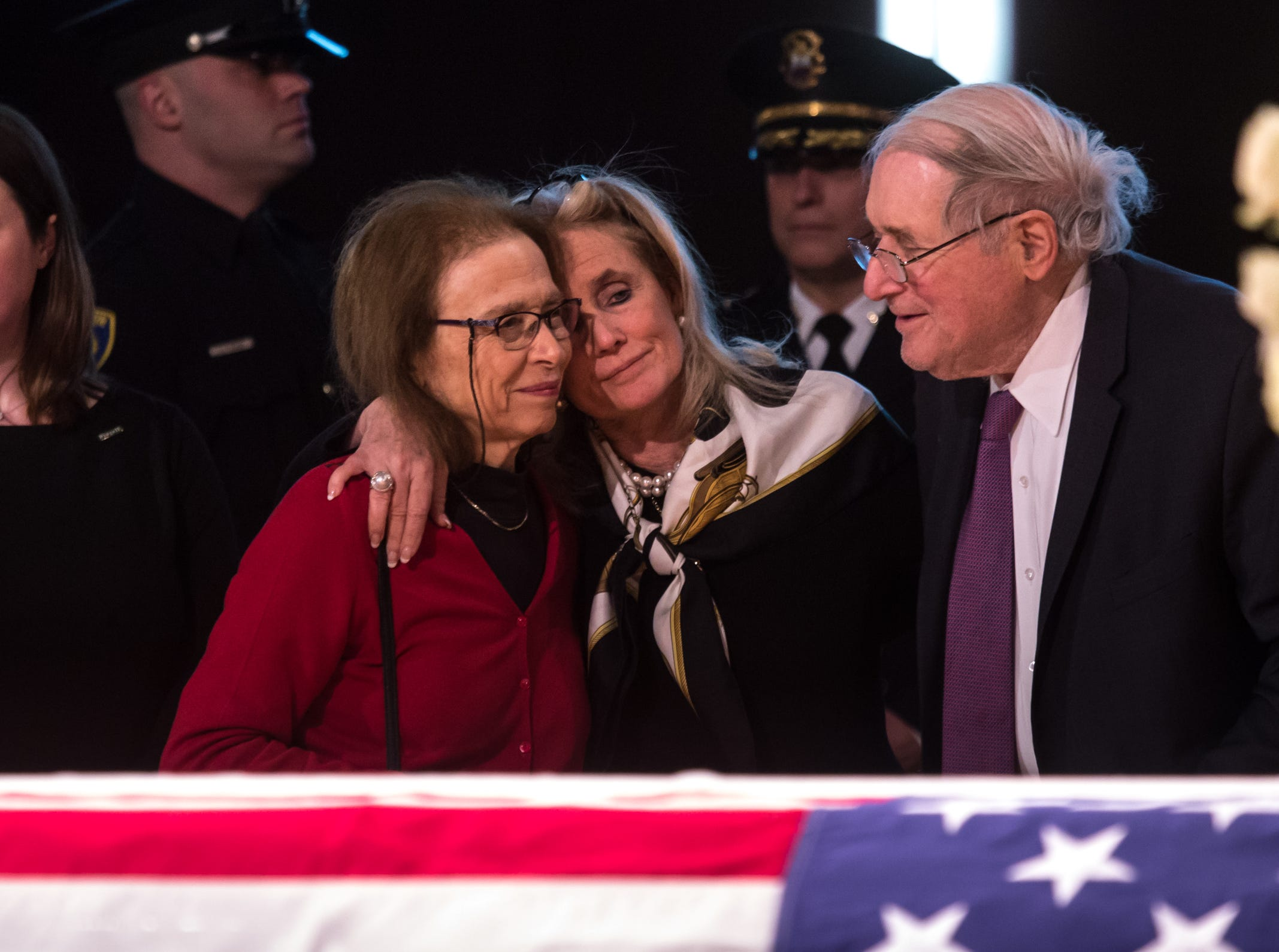 Rep. Debbie Dingell (center) stands with former U.S. Senator Carl Levin and his wife Barbara Levin by the casket of her late husband former U.S. Rep. John D. Dingell during his visitation at the Ford Community and Performing Arts Center in Dearborn on Monday, February 11, 2019.