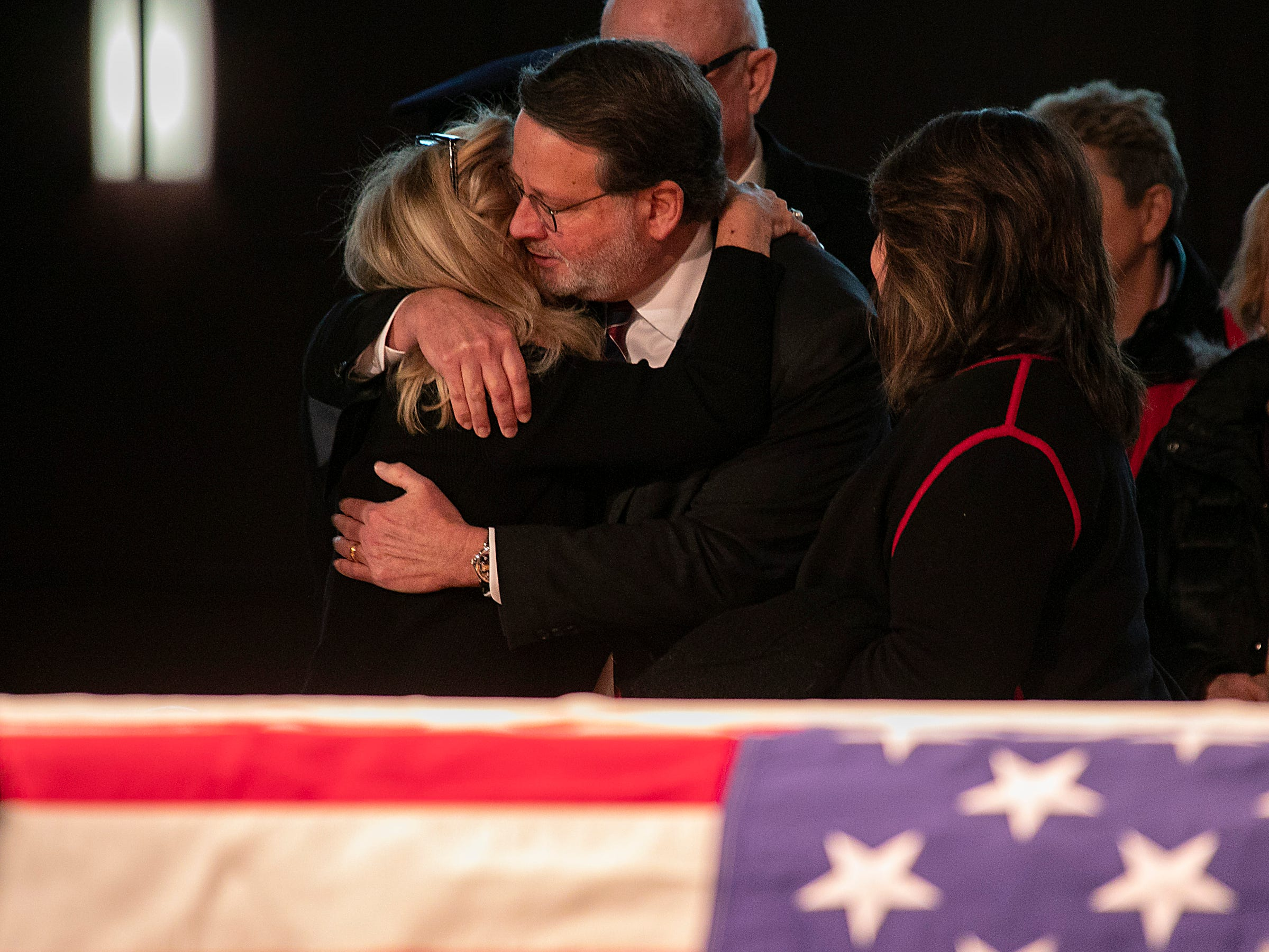 Congresswoman Debbie Dingell, left, greets Senator Gary Peters as visitors stream by to pay their respects to her husband John Dingell who is lying in repose at the Michael A. Guido theater in Dearborn Monday, Feb. 11, 2019.