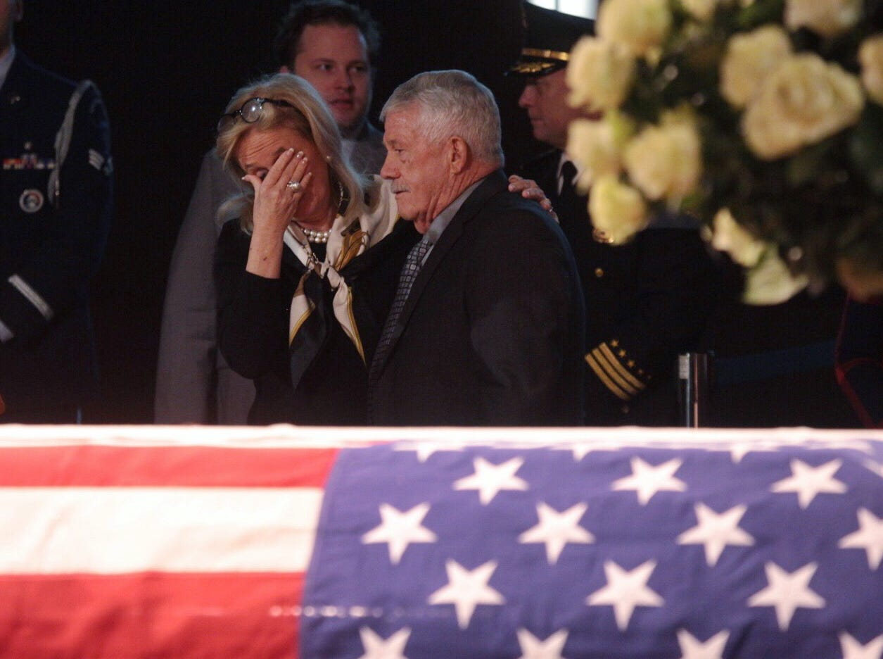 Rep. Debbie Dingell stands by the casket of her late husband former U.S. Rep.  John D. Dingell during his visitation at the Ford Community and Performing Arts Center in Dearborn on Monday, February 11, 2019.
