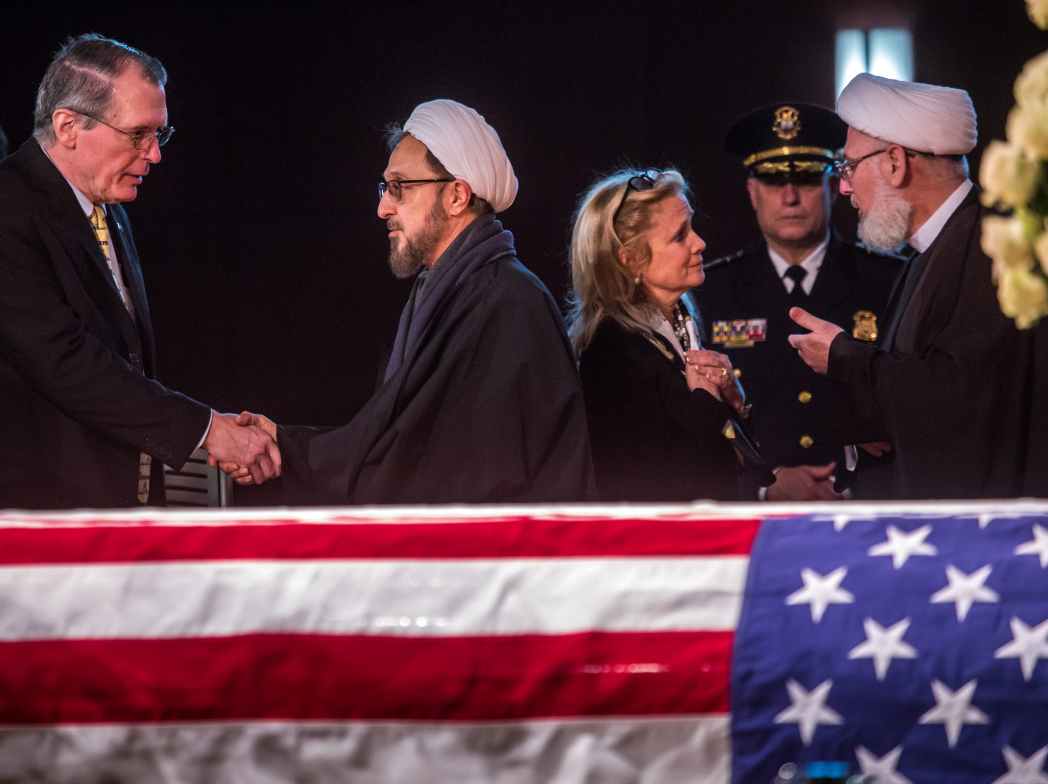 Judge Christopher Dingell, left, shakes hands with Imam Ibrahim Kazerooni of the Islamic Center of America as Rep. Debbie Dingell talks with Imam Ahmad Hammoud of the Islamic Center of America by the casket of her late husband former U.S. Rep. John D. Dingell during his visitation at the Ford Community and Performing Arts Center in Dearborn on Monday, February 11, 2019.
