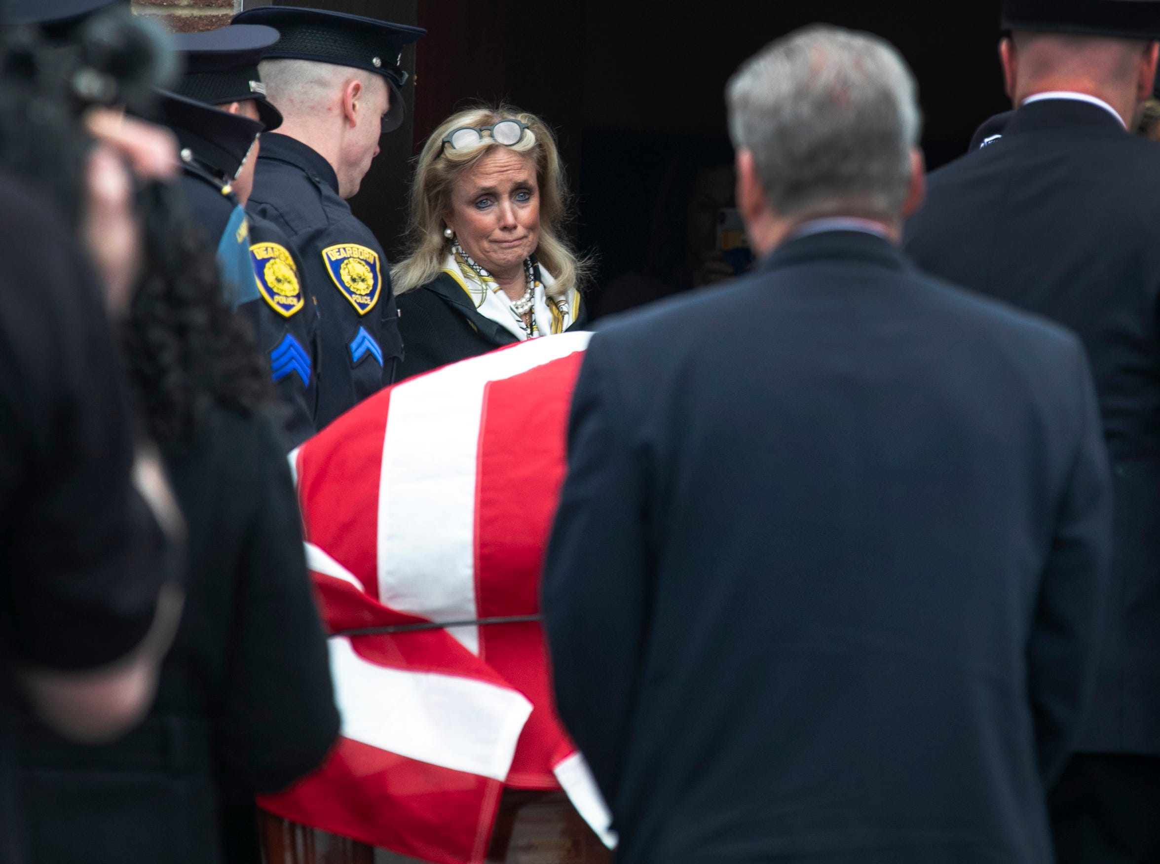 Congresswoman Debbie Dingell watches as the casket carrying her husband John Dingell is brought into the Michael A. Guido theater ahead of a visitation in Dearborn Monday, Feb. 11, 2019.