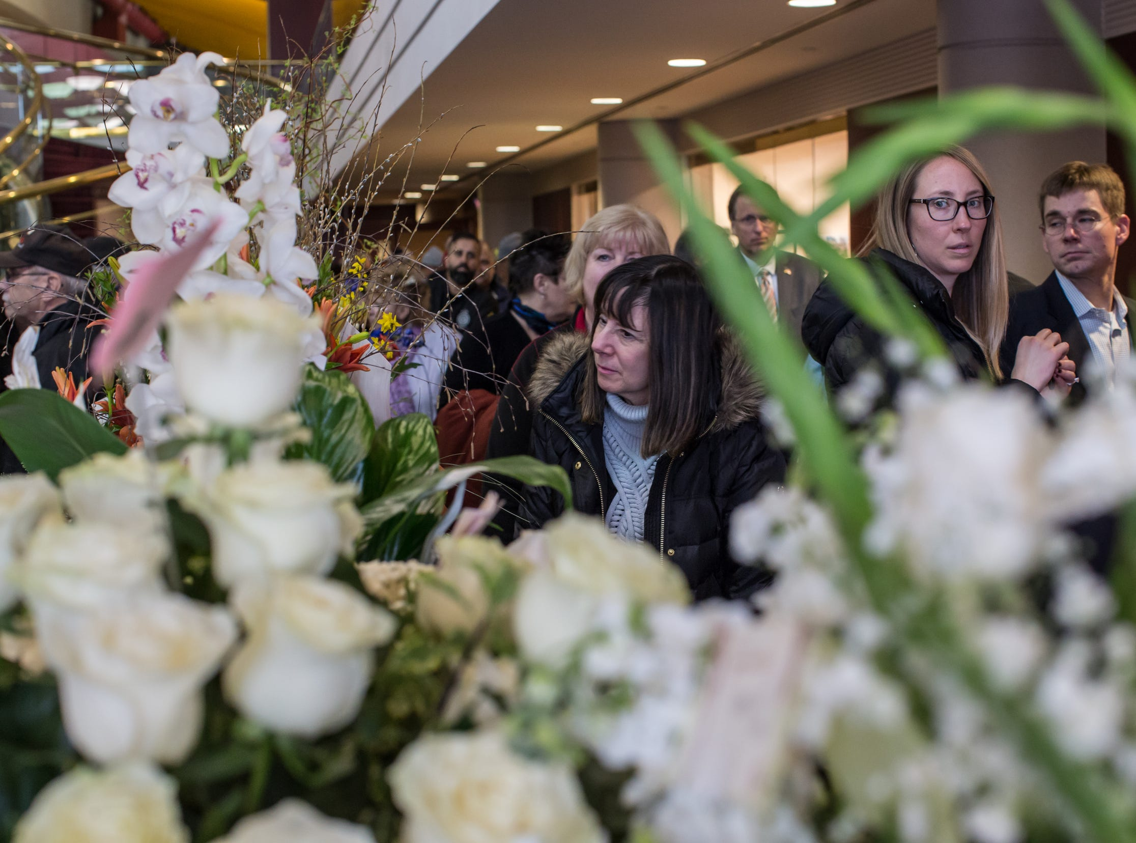 People stand in line amongst flowers sent while waiting to pay their respects during the visitation for the former U.S. Rep. John D. Dingell at the Ford Community and Performing Arts Center in Dearborn on Monday, February 11, 2019.