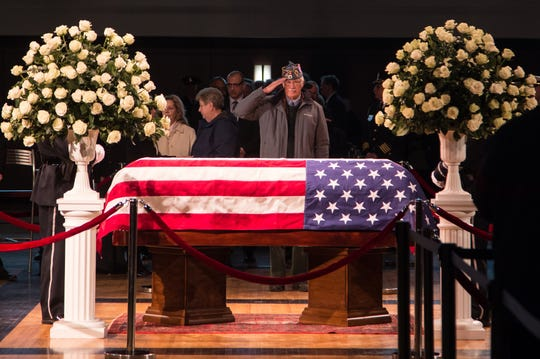 A man salutes the casket of former US Representative John D. Dingell during his visitation at the Ford Community and Performing Arts Center in Dearborn on Monday, February 11, 2019.