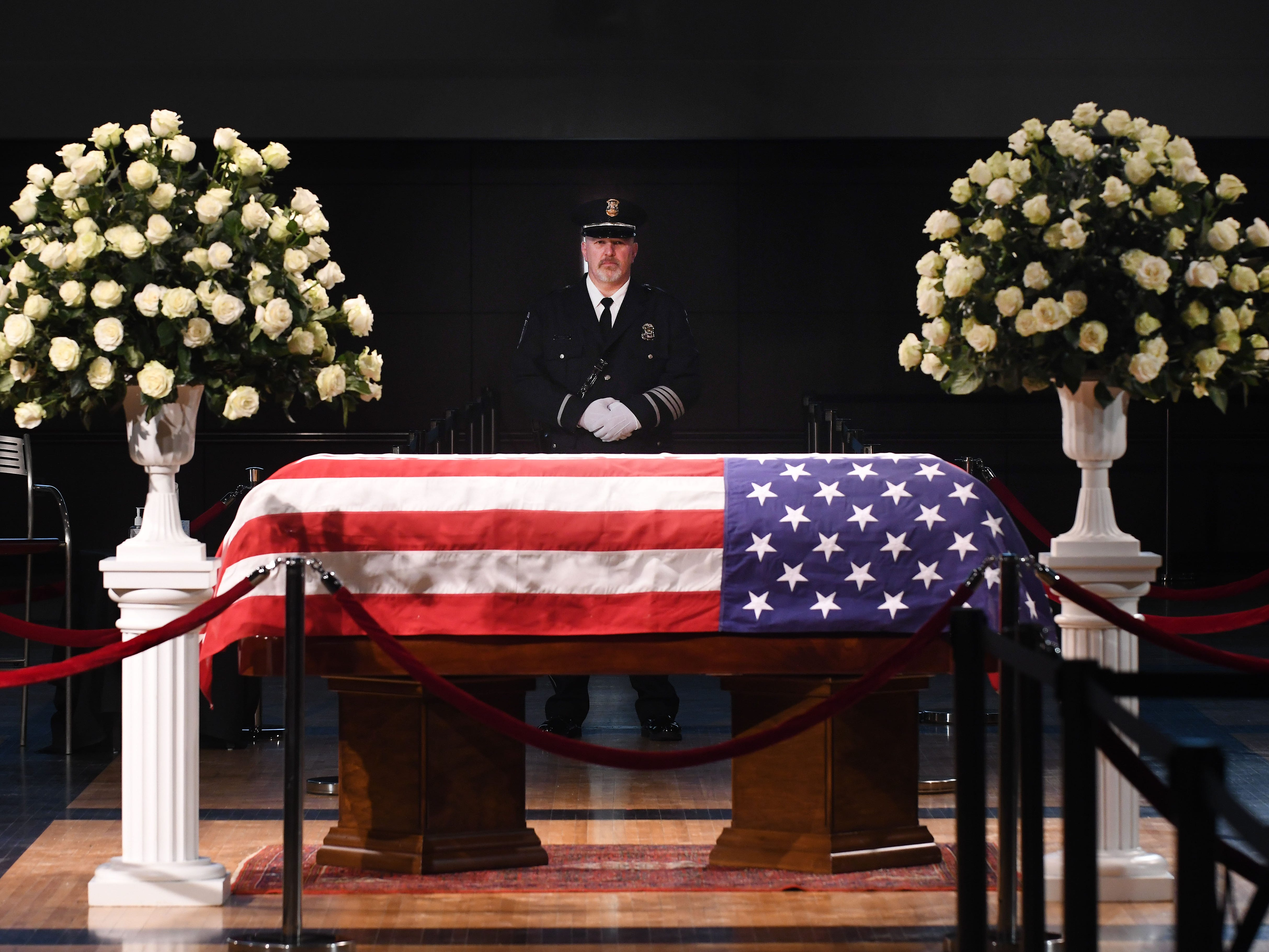 A Dearborn police officer stands behind  the casket of retired U.S. Congressman John D. Dingell.  The Dearborn Democrat  who helped write most of the nation's major environmental and energy laws died Thursday after a battle with cancer. He was 92.