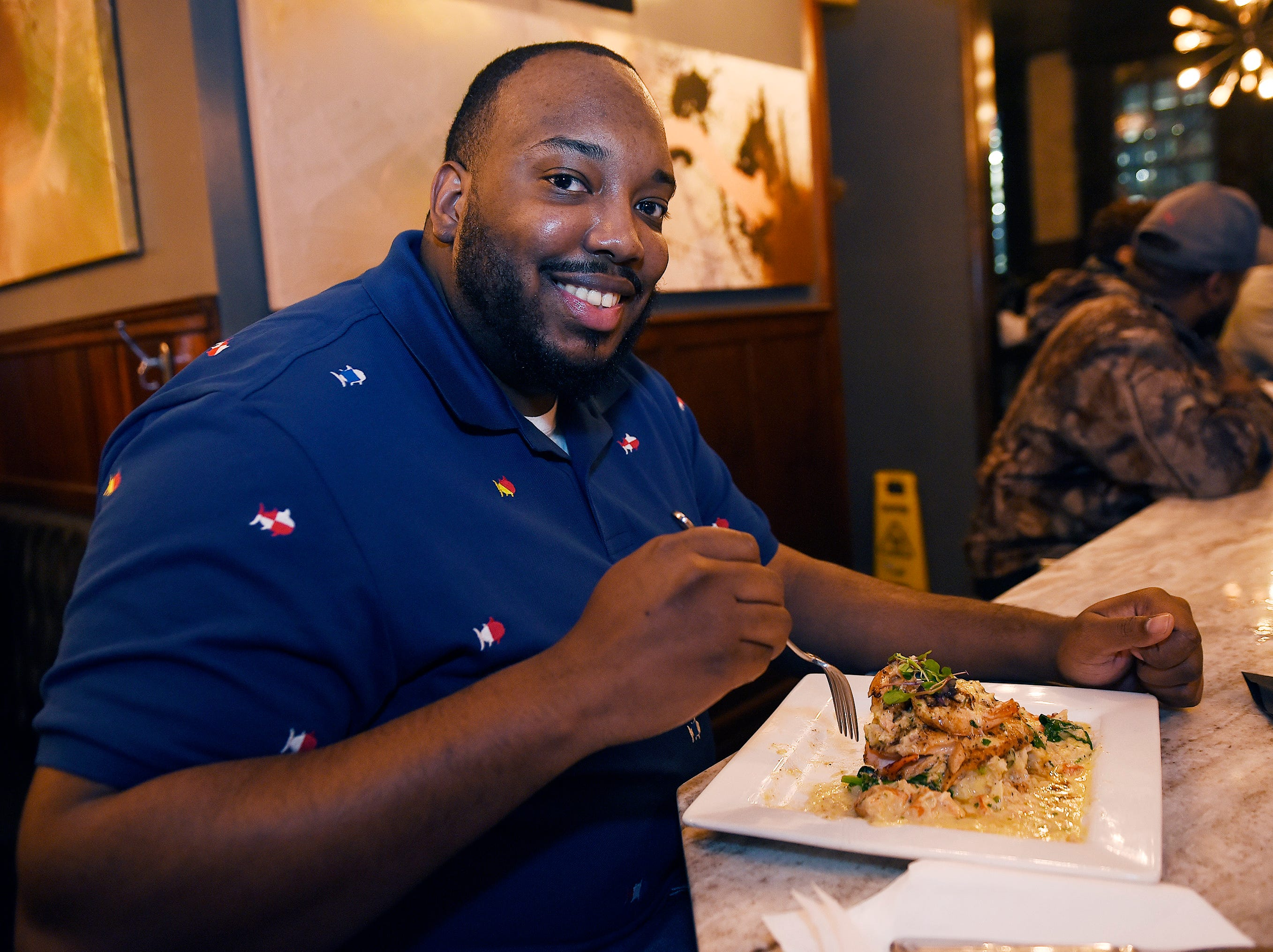 Timothy Collins, 32, of Madison Heights, enjoys his Salmon Tower plate,(8oz organic alaskan salmon, topped with jumbo lump crab & lobster, whipped potatos, spinach with house sauce).