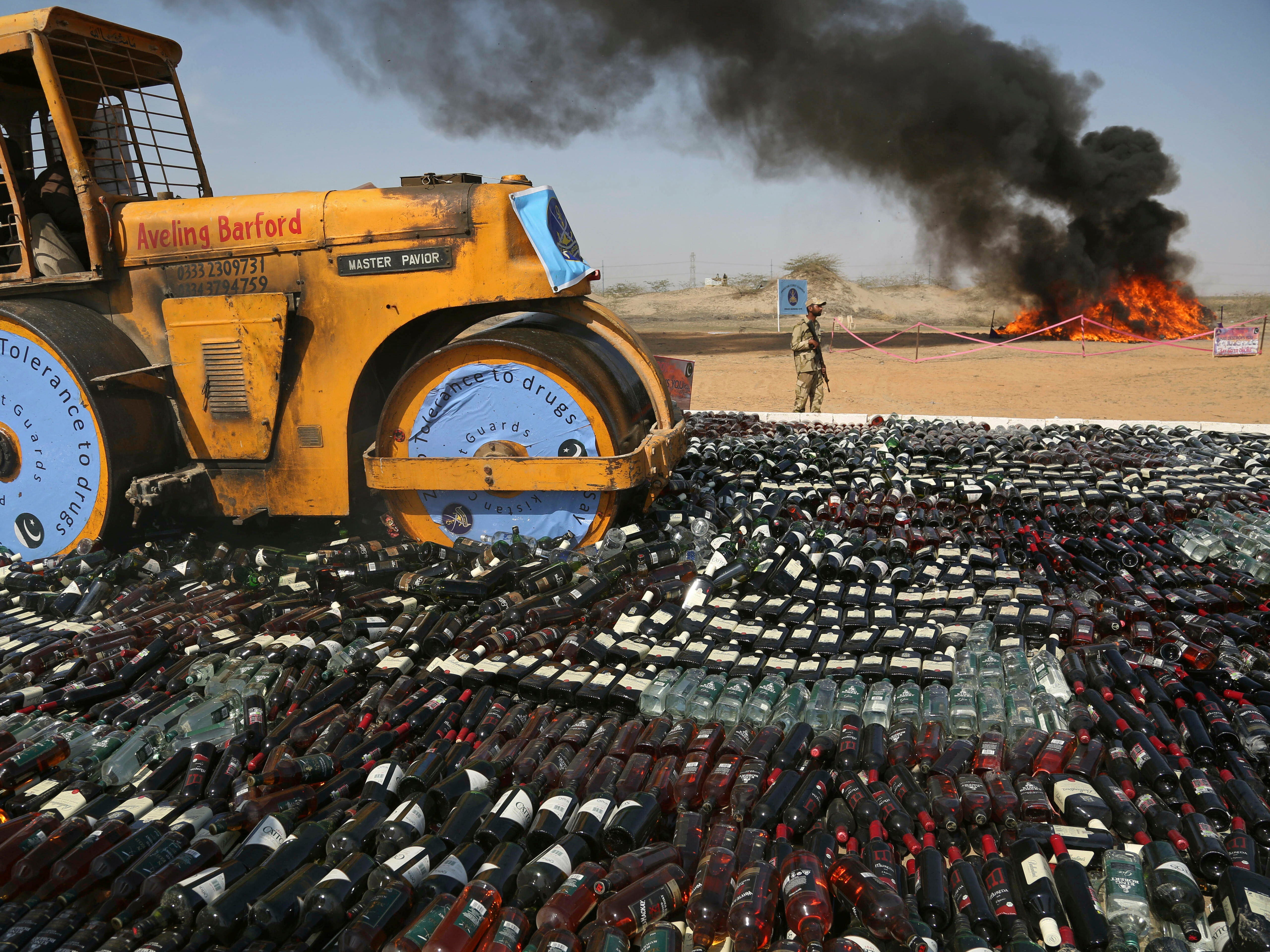 Pakistani authorities smash confiscated bottles of alcohol and burn drugs in Karachi on Monday, Feb. 11, 2019. The Pakistani Anti-Narcotic Force is taking strict measures to stop drug trafficking from neighboring Afghanistan and Pakistani tribal areas.