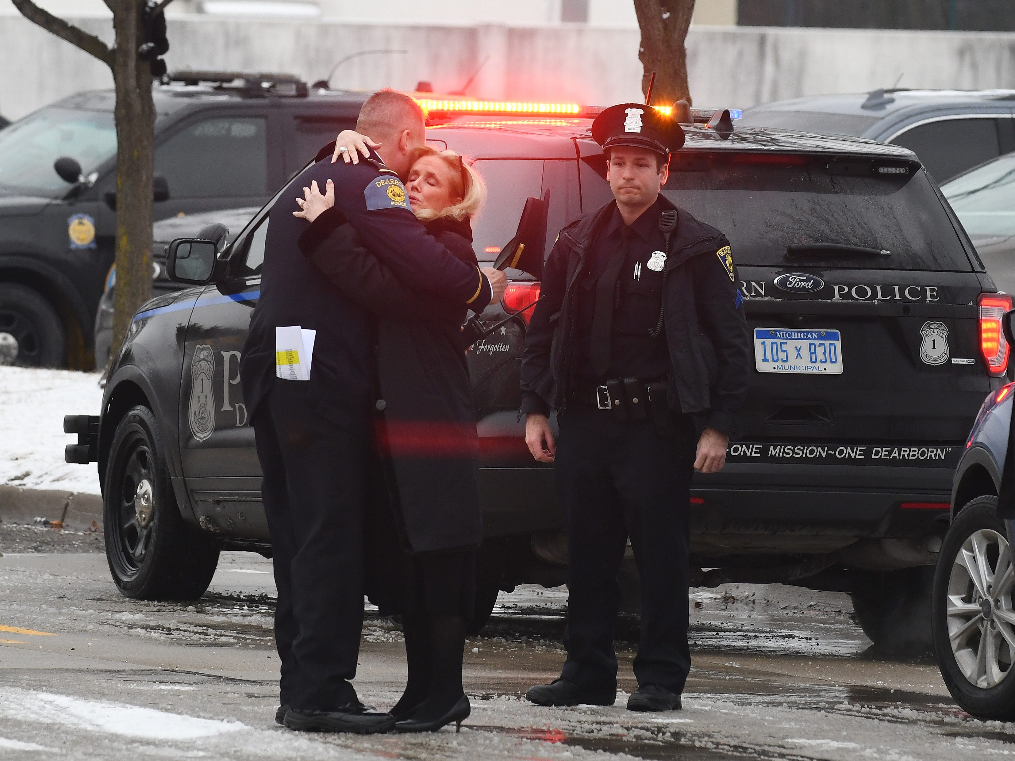 Debbie Dingell hugs several Dearborn police officers prior to the public viewing of her late husband Monday at the Ford Community and Performing Arts Center in Dearborn,.