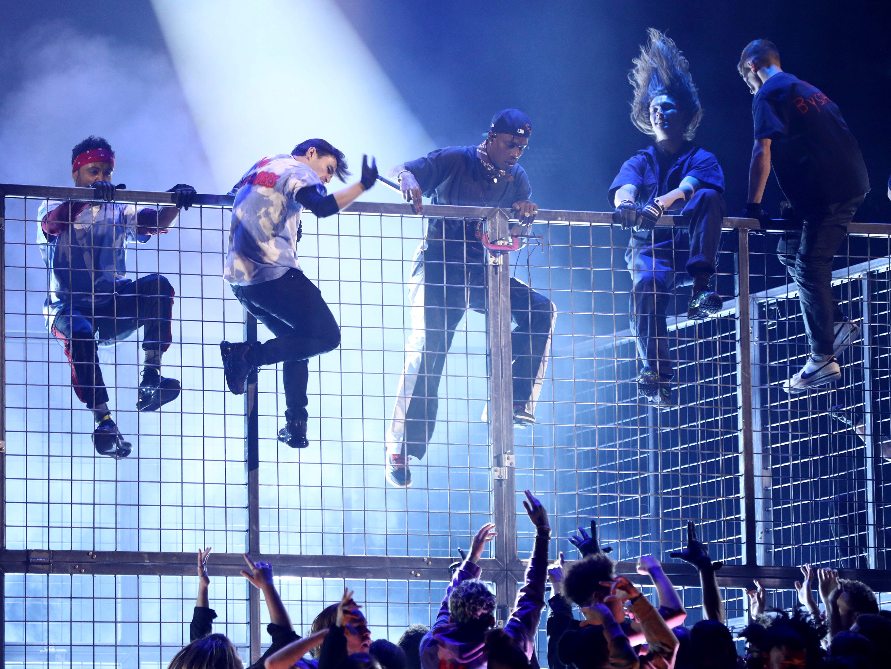 Travis Scott, center, climbs a cage during a performance at the 61st annual Grammy Awards.