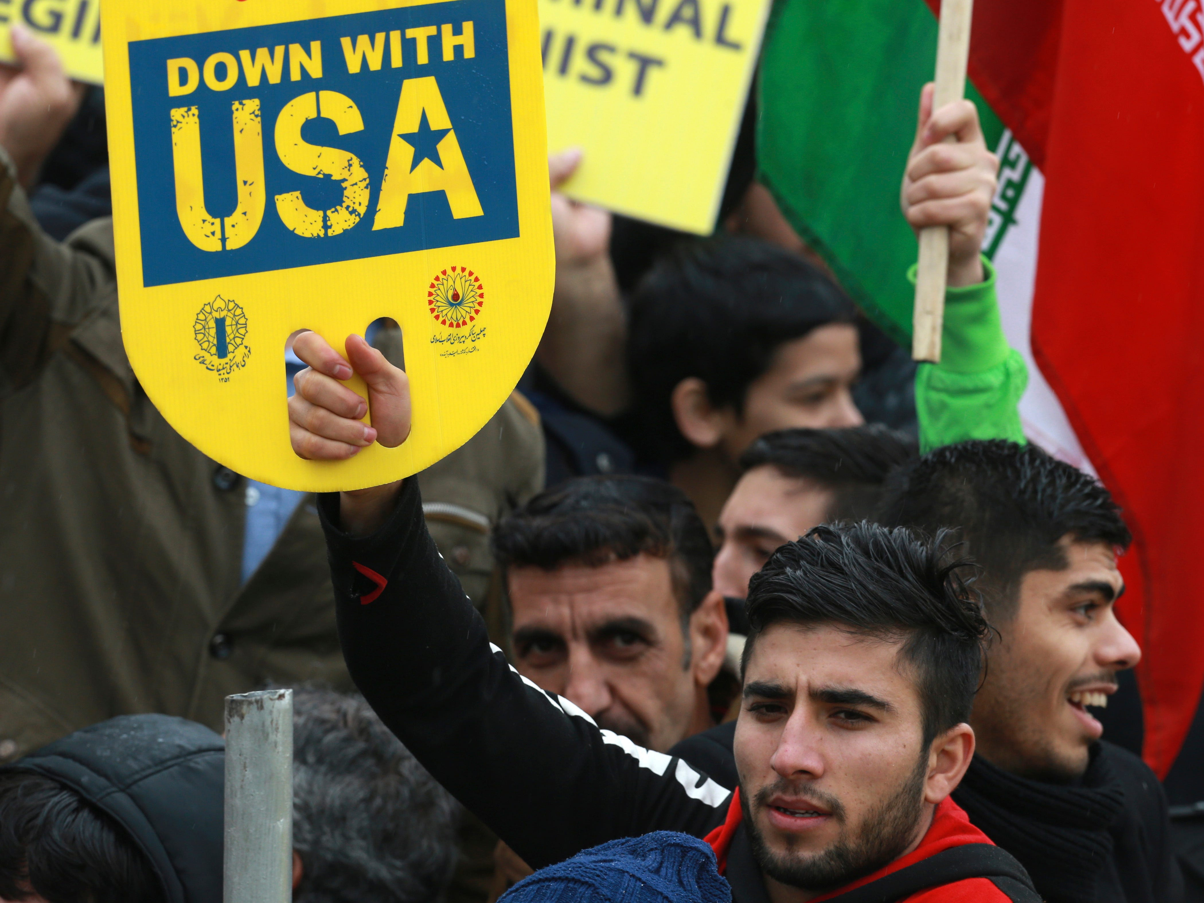 """A demonstrator holds an anti-U.S. placard during a ceremony celebrating the 40th anniversary of the Islamic Revolution, at the Azadi, Freedom, Square in Tehran on Monday, Feb. 11, 2019. Crowds streamed in the rain from a dozen of the capital's far-flung neighborhoods to mass in central Tehran, waving Iranian flags and chanting """"Death to America,"""" a refrain that has been standard fare at anti-U.S. rallies across Iran."""