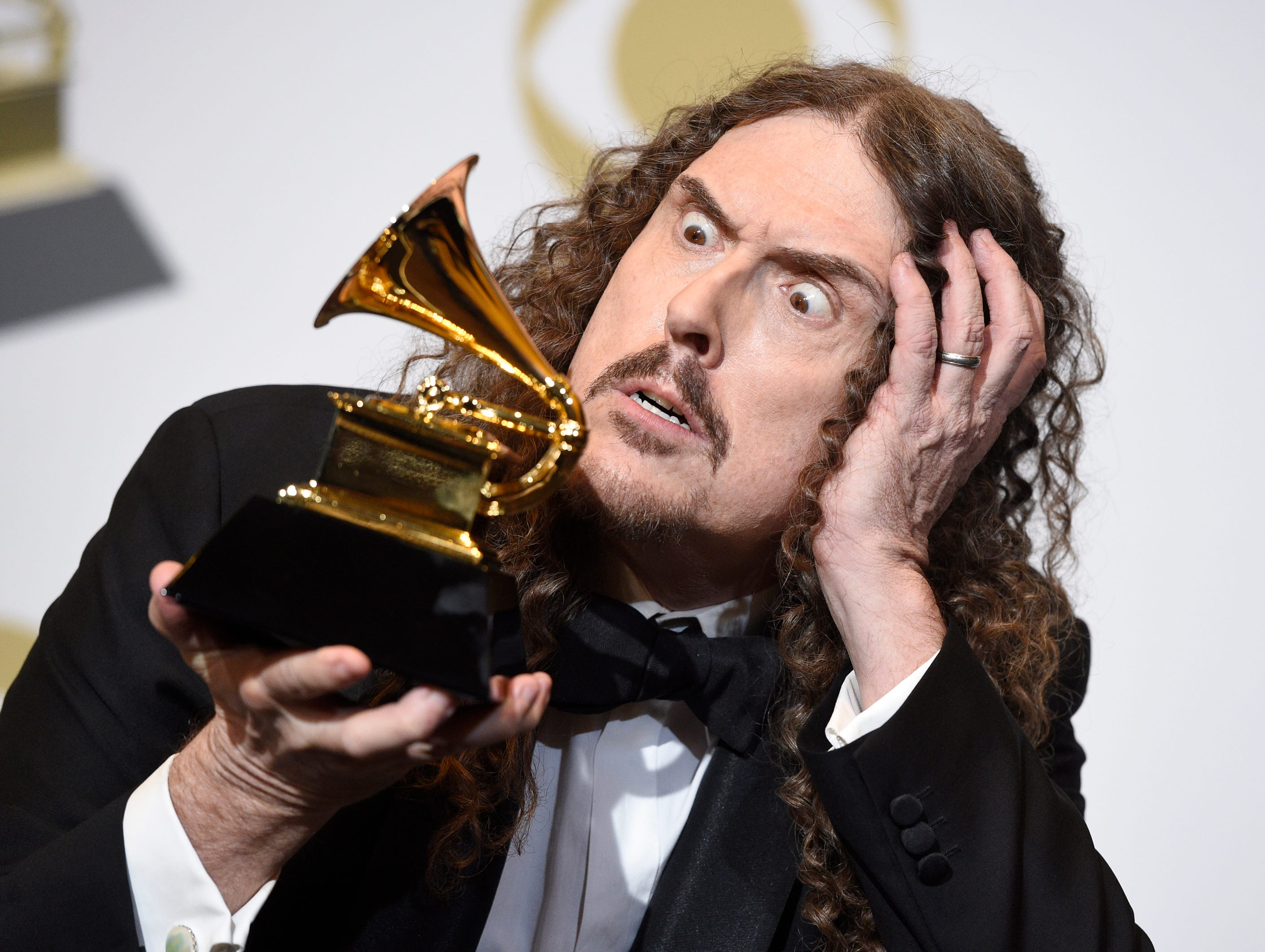 """Weird Al"" Yankovic poses in the press room with the award for best boxed or special limited edition package for ""Squeeze Box: The Complete Works of 'Weird Al' Yankovic"" at the 61st annual Grammy Awards."